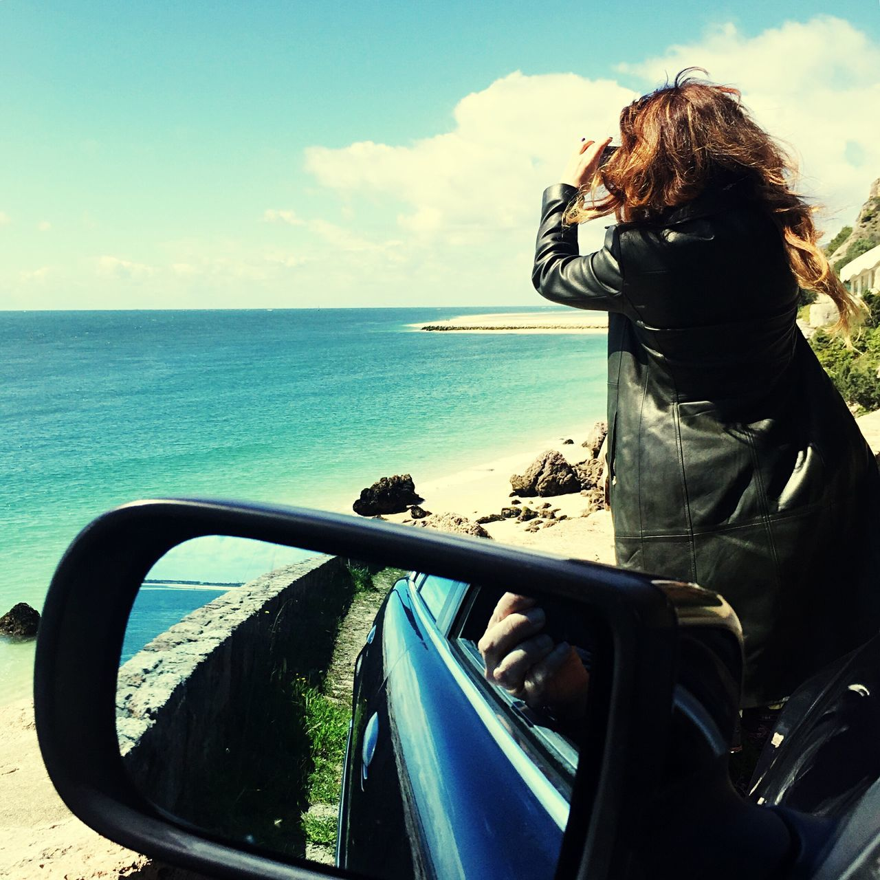 Rear View Of Woman On Car Photographing Sea