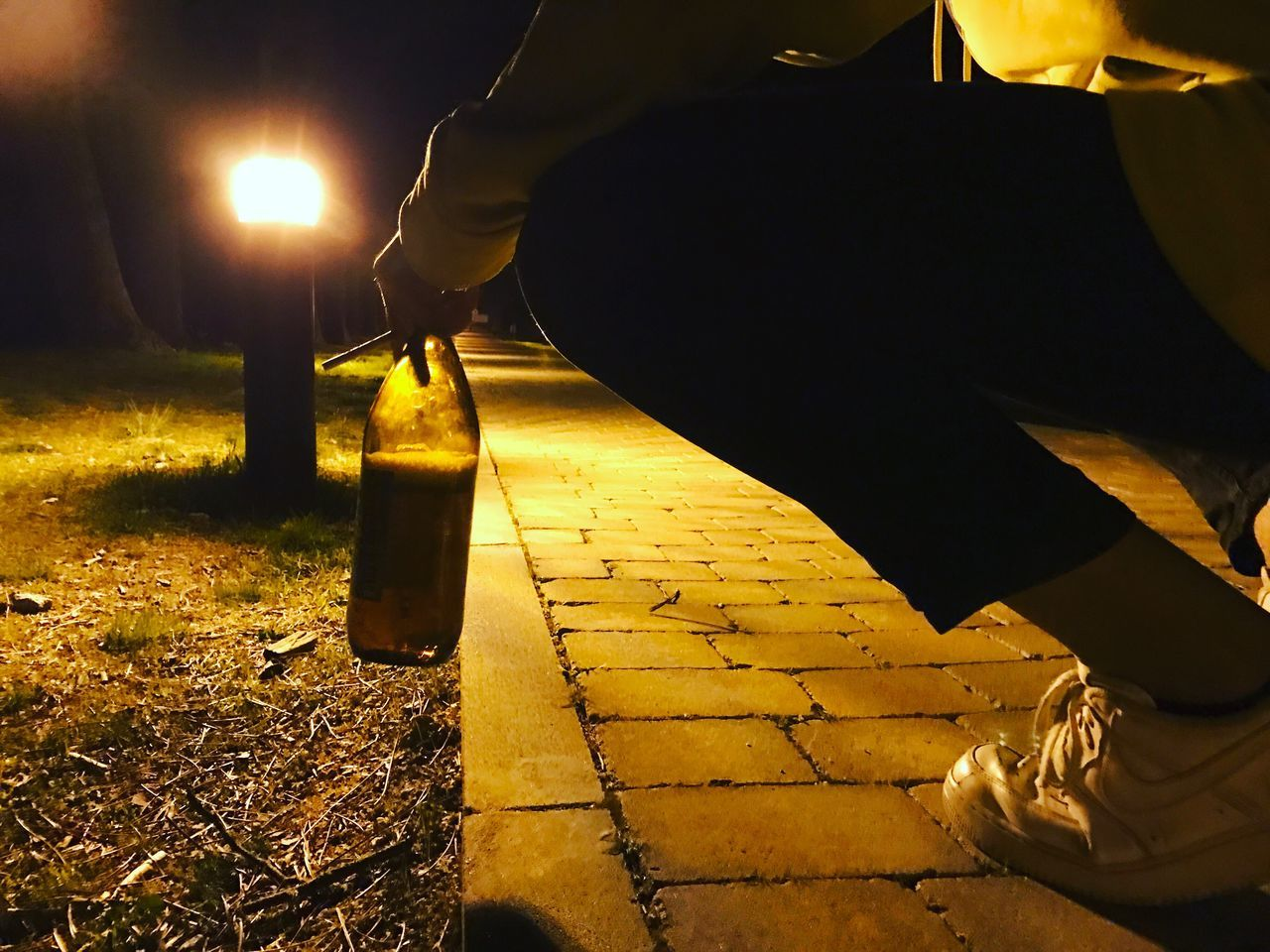 low section, night, one person, illuminated, bottle, real people, holding, human leg, outdoors, men, close-up, human body part, human hand, people