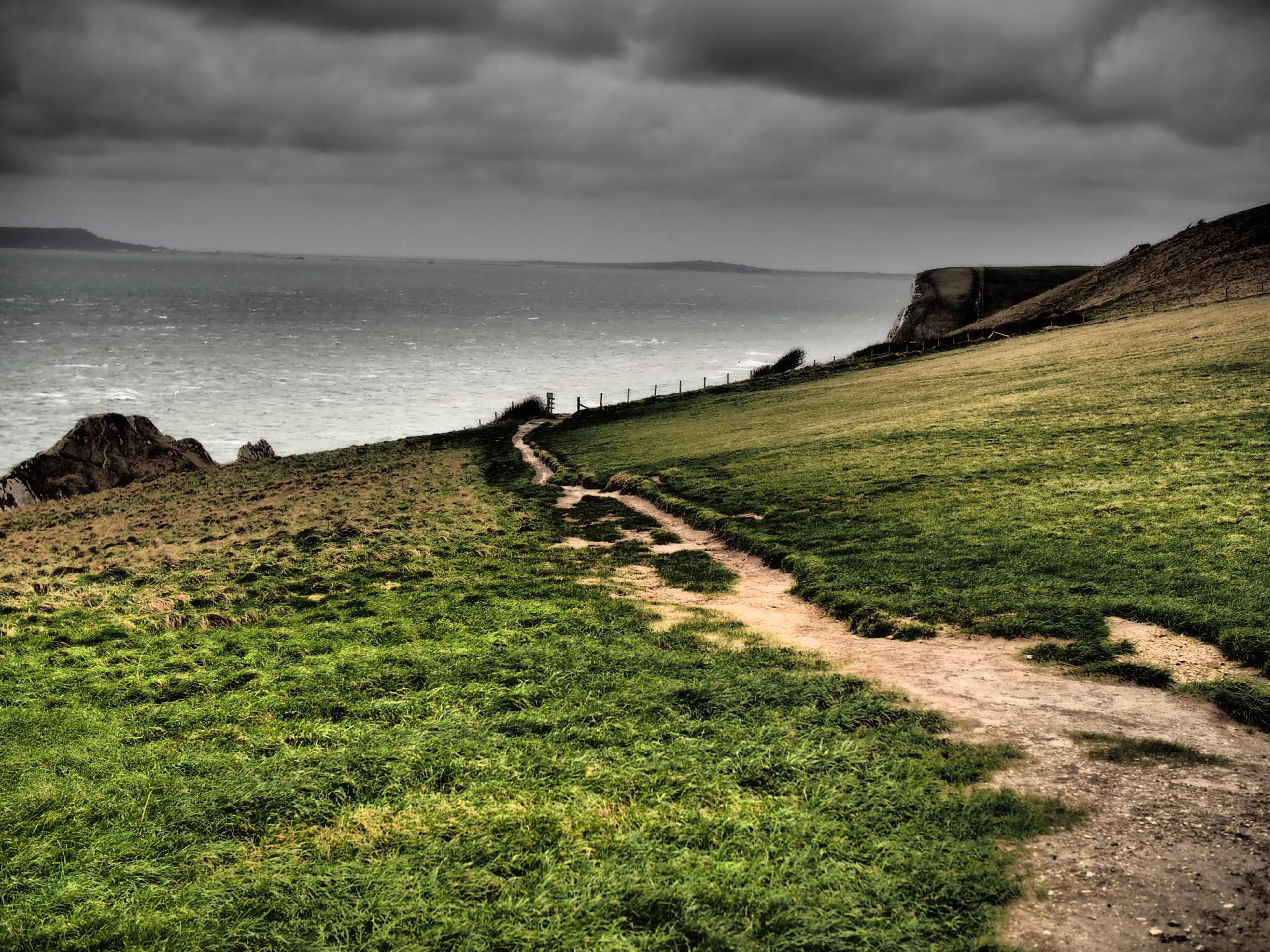 sky, grass, tranquil scene, tranquility, sea, horizon over water, scenics, cloud - sky, beauty in nature, nature, landscape, water, cloud, cloudy, beach, field, remote, grassy, idyllic, non-urban scene