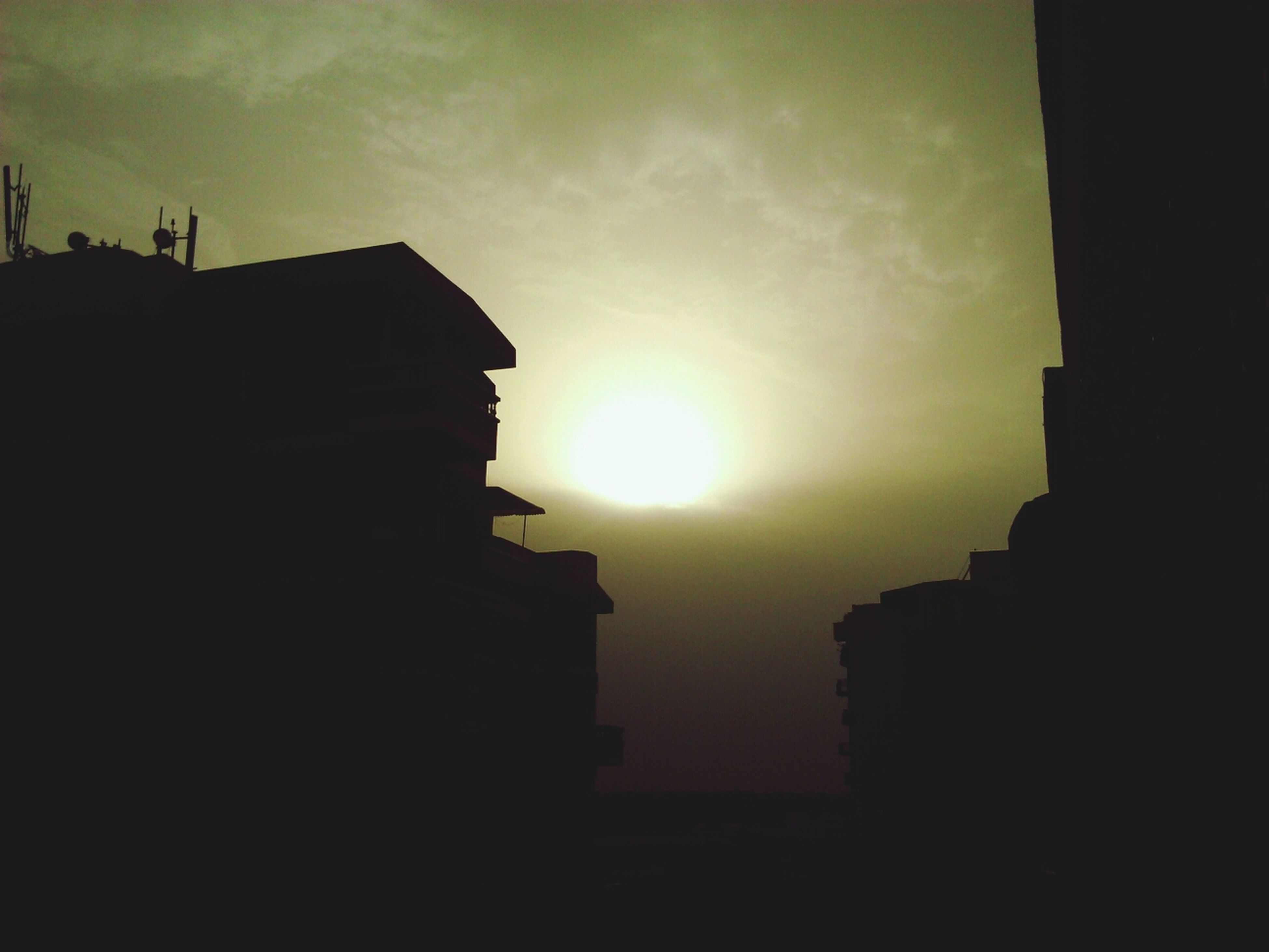 building exterior, architecture, built structure, sun, silhouette, sunset, sky, low angle view, sunlight, sunbeam, building, lens flare, residential structure, house, residential building, city, cloud - sky, outdoors, no people, cloud
