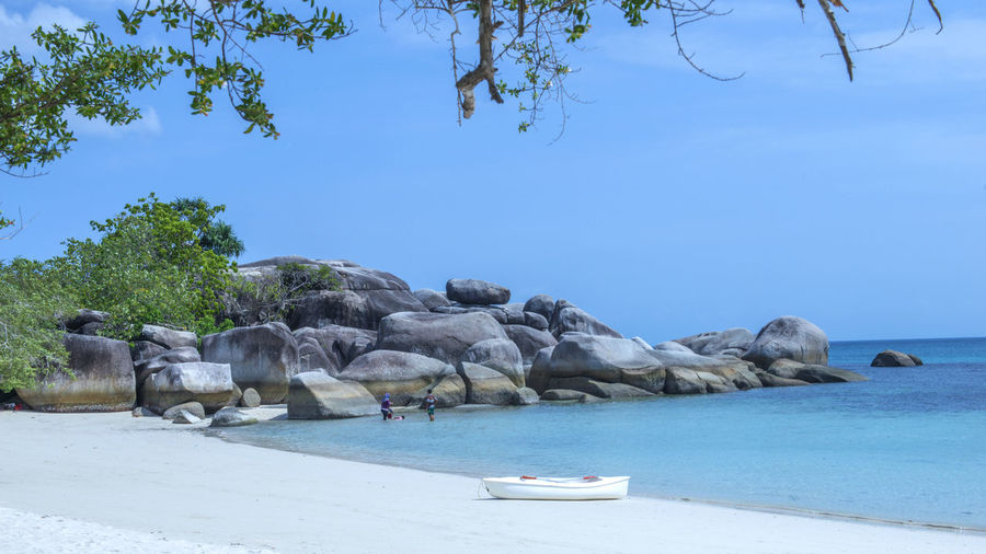 A white fibre glass canoe lays on white sandy beach against a bright blue sky & rocky sea stack Beach Belitung Belitung, Indonesia Blue Boat Day Idyllic Scenery Landscape Nature Nautical Vessel No People Outdoors Palm Tree Pedal Boat Rock & Water Rock Formation Rock Stacking Scenic Landscapes Scenic Lookout Scenic View Scenicphotography Summer Tree Vacation Time Water