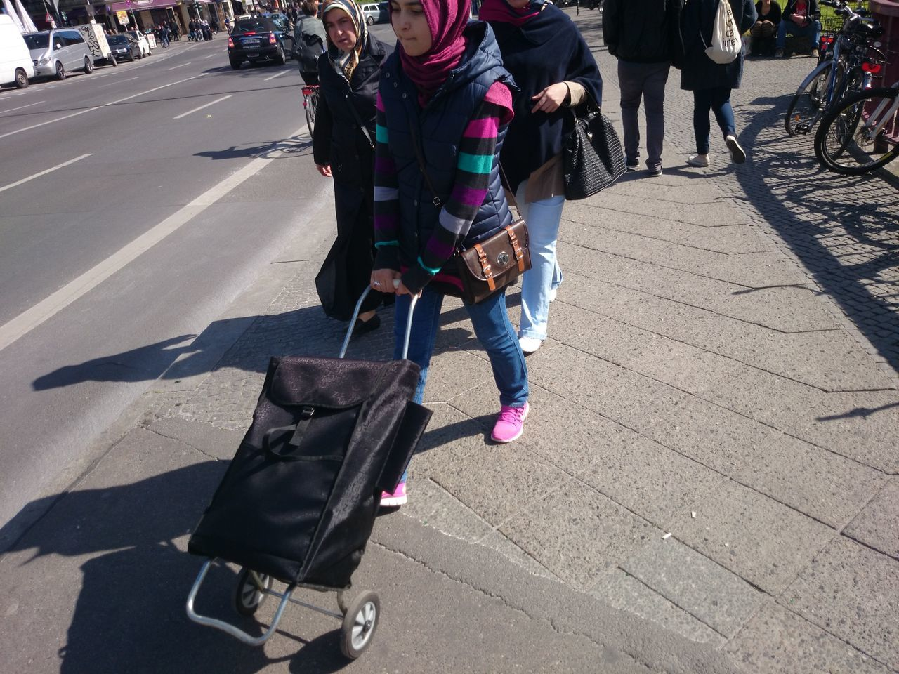 transportation, street, outdoors, travel, luggage, walking, riding, real people, mode of transport, day, road, sunlight, city, bicycle, land vehicle, baby stroller, lifestyles, women, low section, shadow, men, pedestrian, one person, people, adult