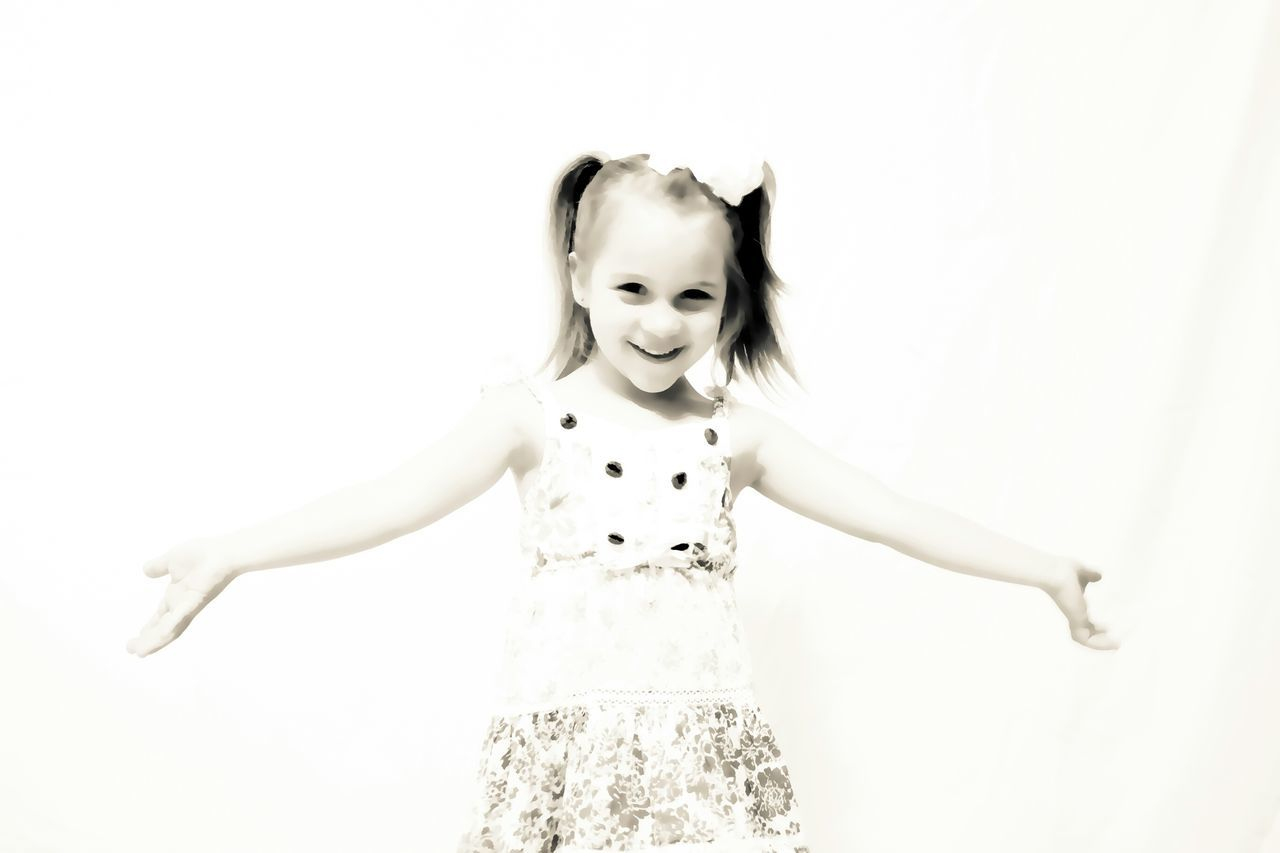 Portrait Of Cute Girl With Arms Outstretched Standing Against Wall