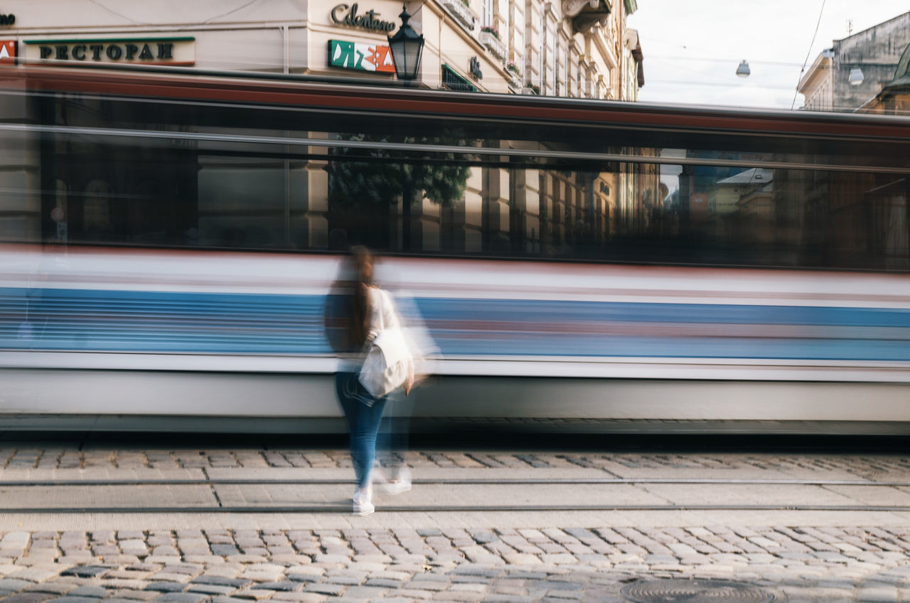 The girl is ahead of the tram to the main square of Lviv. Long exposure Blurred Motion Long Exposure Lviv Motion One Person Passenger Train Public Transportation Rail Transportation Railroad Track Real People Speed Streetphotography Train - Vehicle Tram Transportation Travel Travel Destinations Ukraine