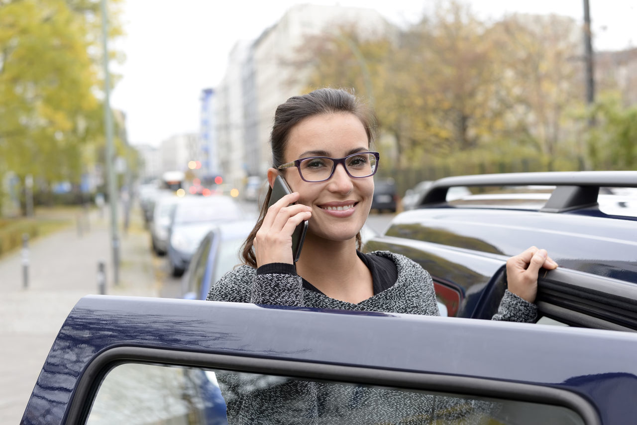 businesswoman with smartphone Automobile Business Businesswoman Car Cellphone City Confidence  Connect Glasses Happy Hearing Laughing Listening Manager Mobile Phone Smartphone Smiling Speaking Successful Technology Telephone Urban Vehicle Woman