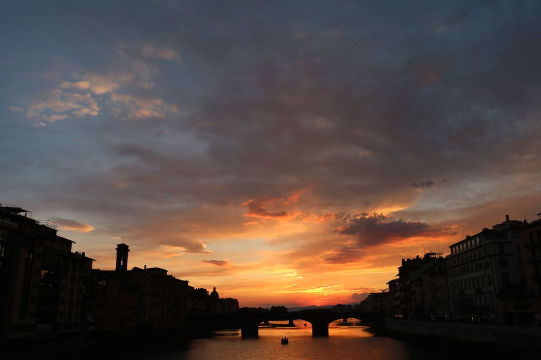 The setting sky forming silhouettes of buildings lining the water and the bridge from Ponte Vecchio in Florence, Italy Colours Dark Pink Red Reflection Silhouette Travel Boat Bridge Buildings Clouds Dusk Evening Florence Hues Italy Opposite Orange Color Shadow Sky Sunset Tinge Vibrant Water Yellow