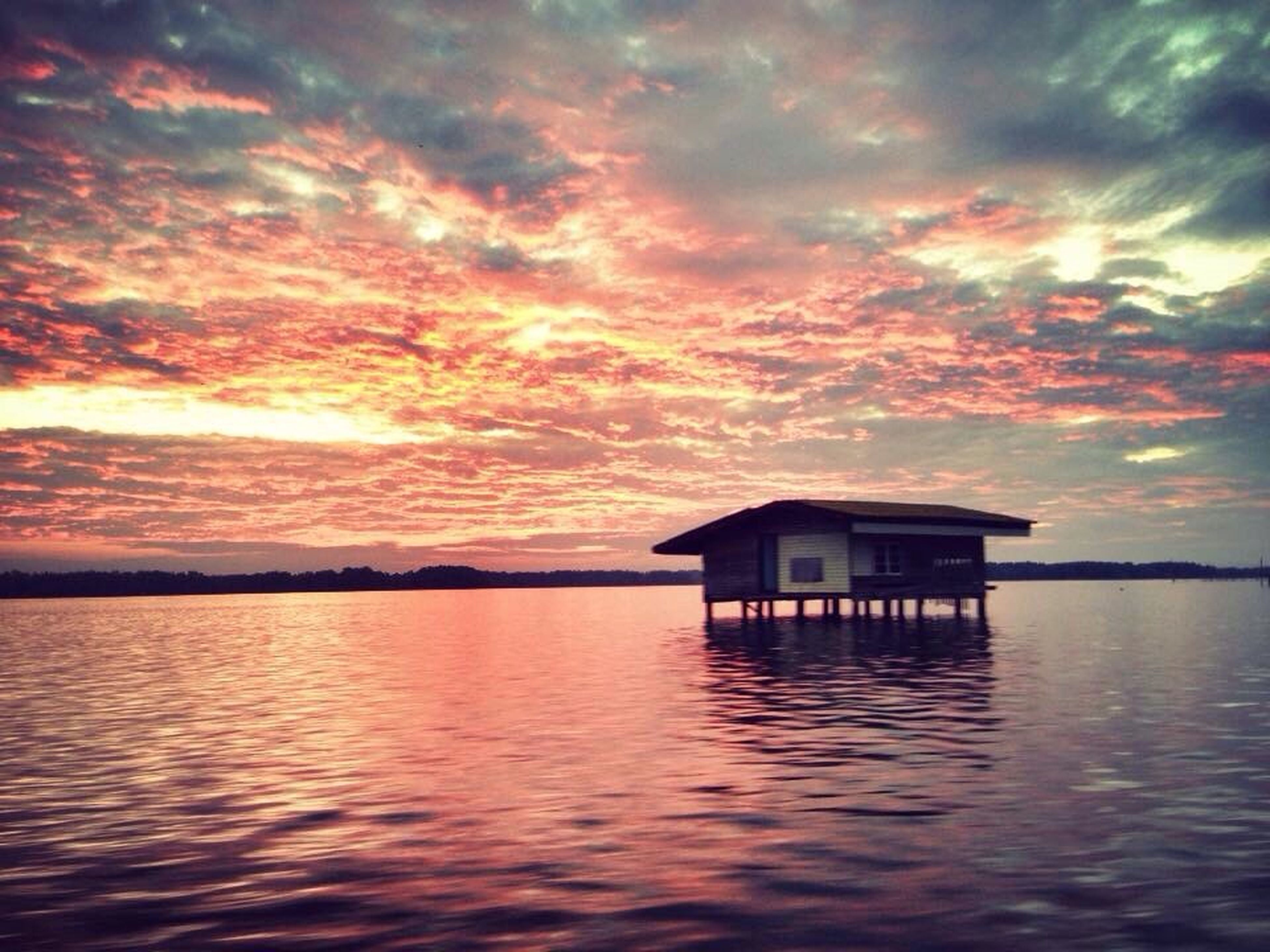 sunset, water, waterfront, sky, built structure, architecture, building exterior, cloud - sky, scenics, tranquil scene, beauty in nature, tranquility, reflection, rippled, cloudy, cloud, orange color, house, sea, idyllic