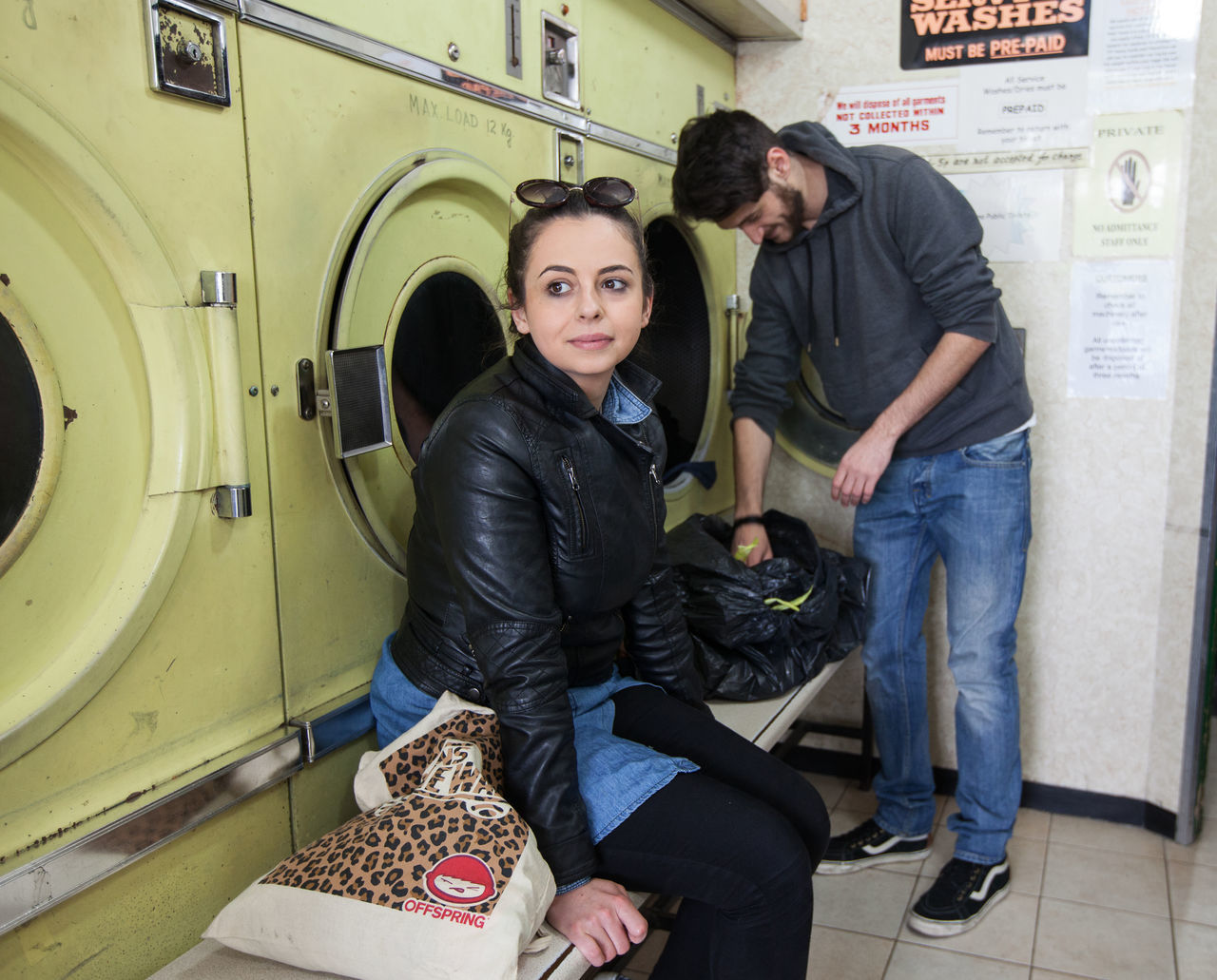 two people, young women, young adult, young men, casual clothing, real people, washing machine, laundromat, day, standing, sitting, smiling, full length, lifestyles, women, men, cheerful, indoors, togetherness, well-dressed, adult, people