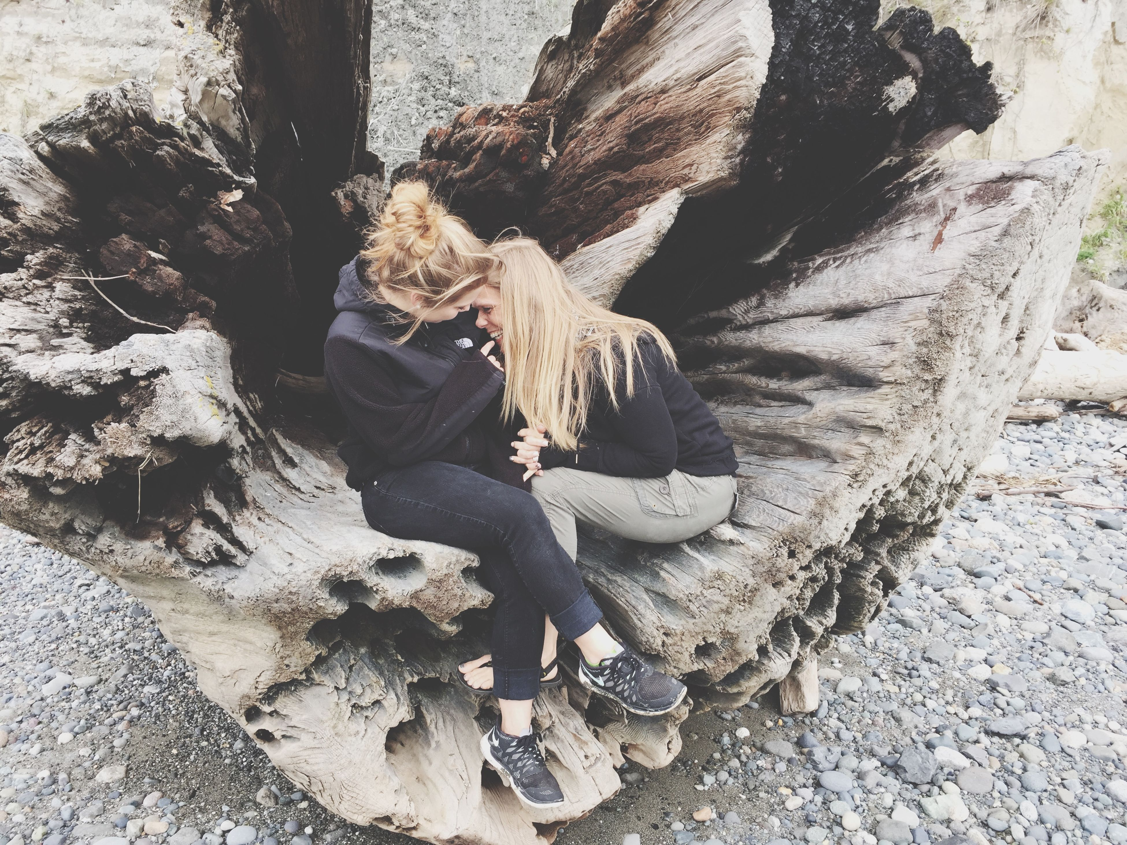 tree trunk, rock - object, sunlight, full length, tree, day, outdoors, nature, shadow, lifestyles, leisure activity, high angle view, rock formation, sitting, textured, rock, standing, casual clothing