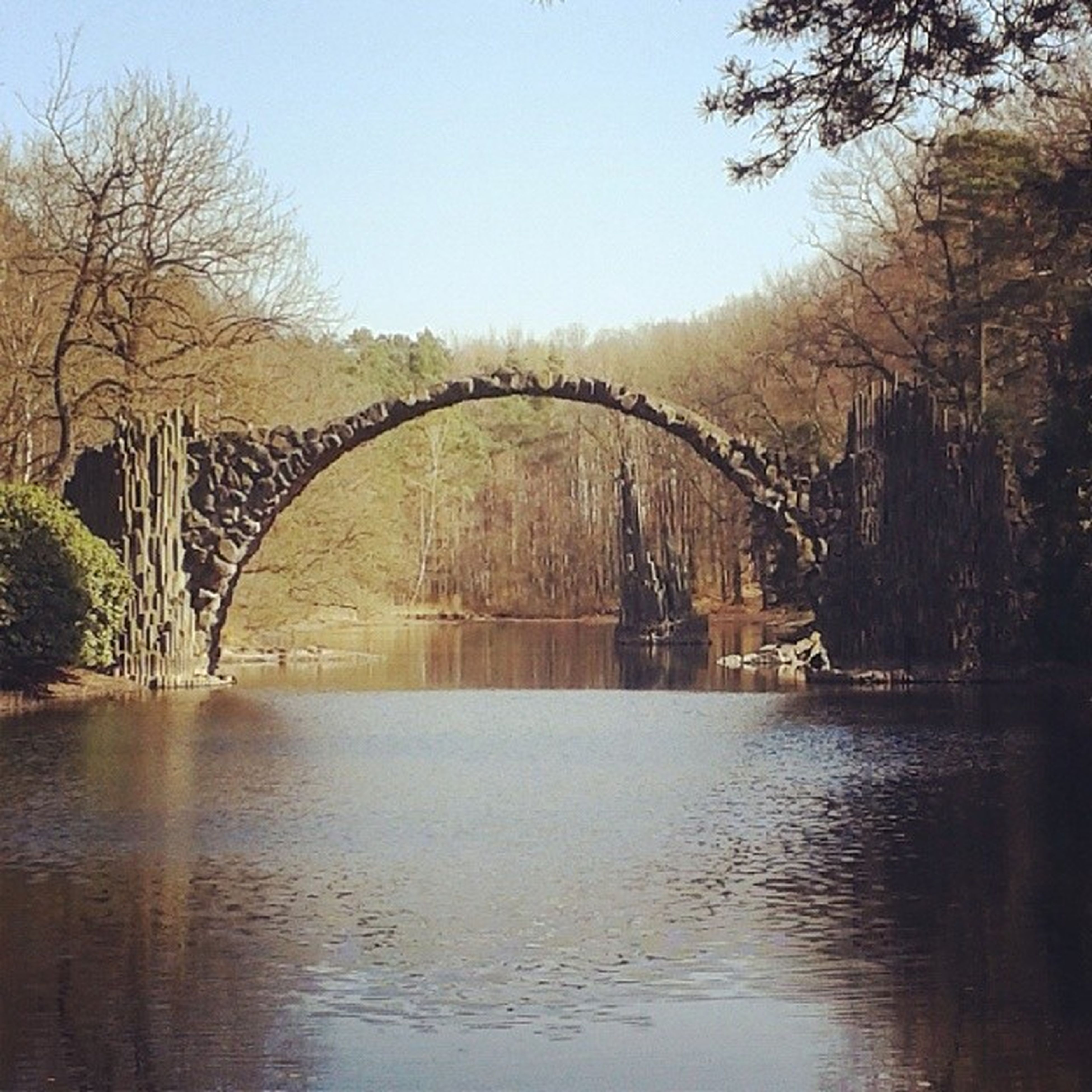 connection, bridge - man made structure, built structure, architecture, tree, water, river, arch bridge, bridge, reflection, waterfront, clear sky, arch, tranquility, bare tree, engineering, lake, tranquil scene, nature, sky