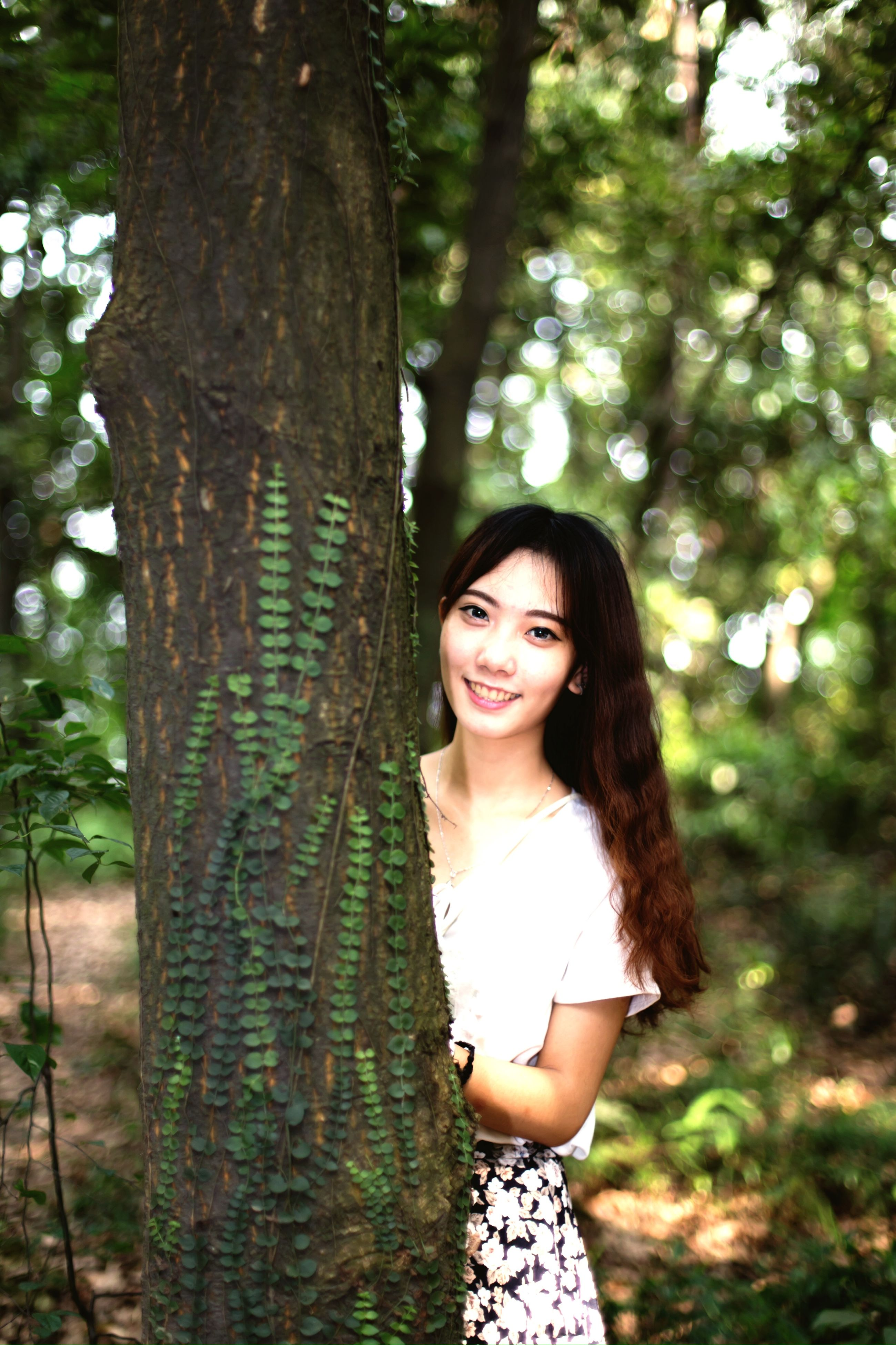 young adult, young women, tree, portrait, looking at camera, person, long hair, lifestyles, front view, leisure activity, focus on foreground, smiling, casual clothing, forest, tree trunk, beauty, standing
