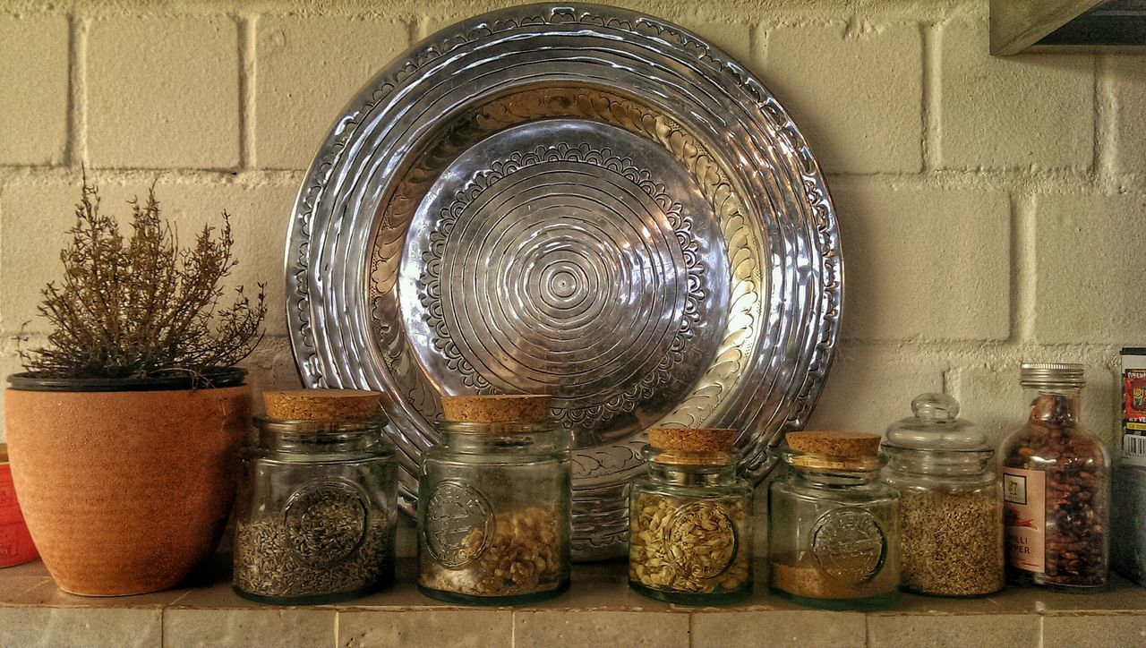 Close-Up Of Glass Jars Against The Wall