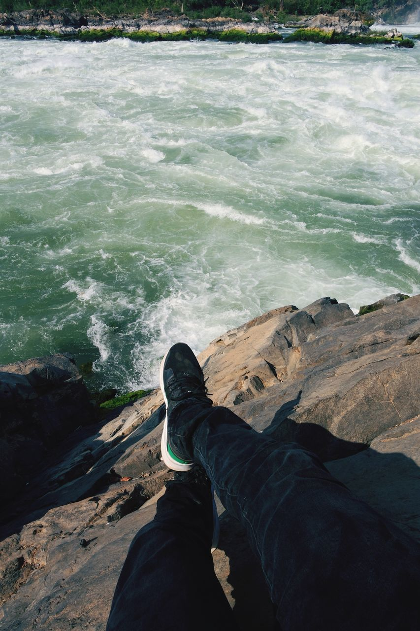 water, sea, wave, rock - object, one person, day, human leg, nature, low section, outdoors, sitting, human body part, real people, beauty in nature, people