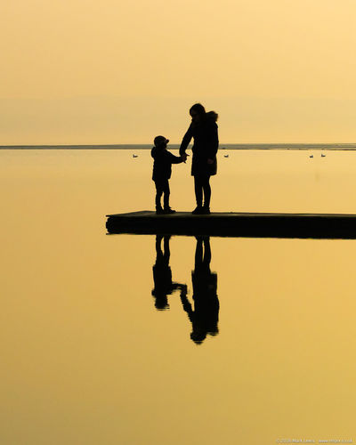 A mothers touch Clear Sky Comfort Comforting Hands Holding Mother Orange Color Person Real People Reassurance Reassure Reflection Silhouette Standing Sunset Togetherness Touch Tranquility Water