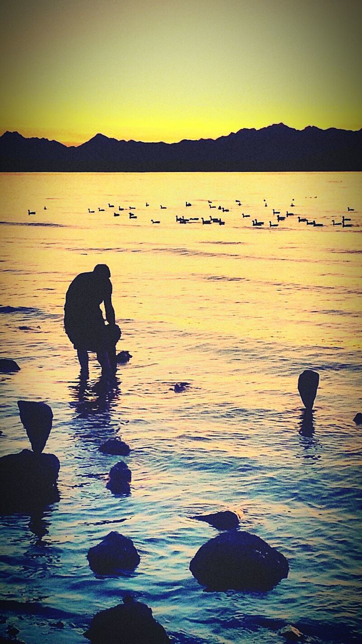 Silhouette Of Men On Beach Bending To Pick Up Stones