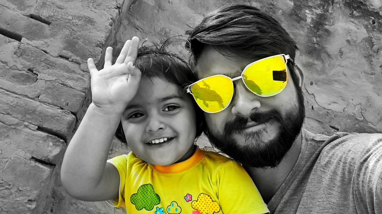 two people, headshot, togetherness, real people, childhood, portrait, yellow, looking at camera, happiness, smiling, day, bonding, leisure activity, outdoors, lifestyles, close-up, adult, people