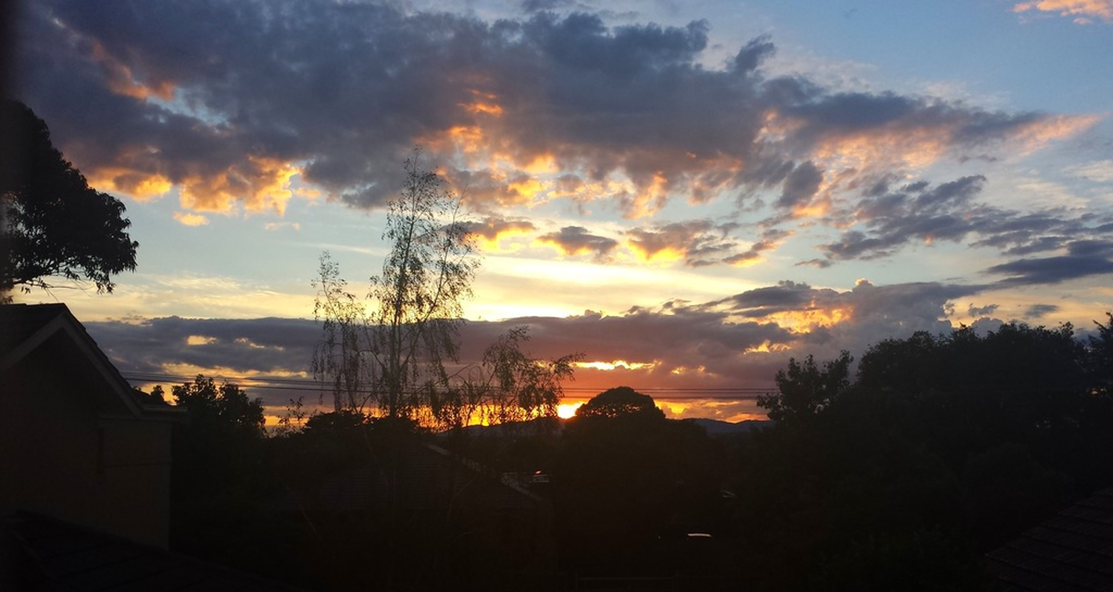 sunset, sky, silhouette, cloud - sky, building exterior, scenics, beauty in nature, cloudy, orange color, tree, built structure, cloud, architecture, dramatic sky, house, tranquil scene, nature, tranquility, idyllic, moody sky