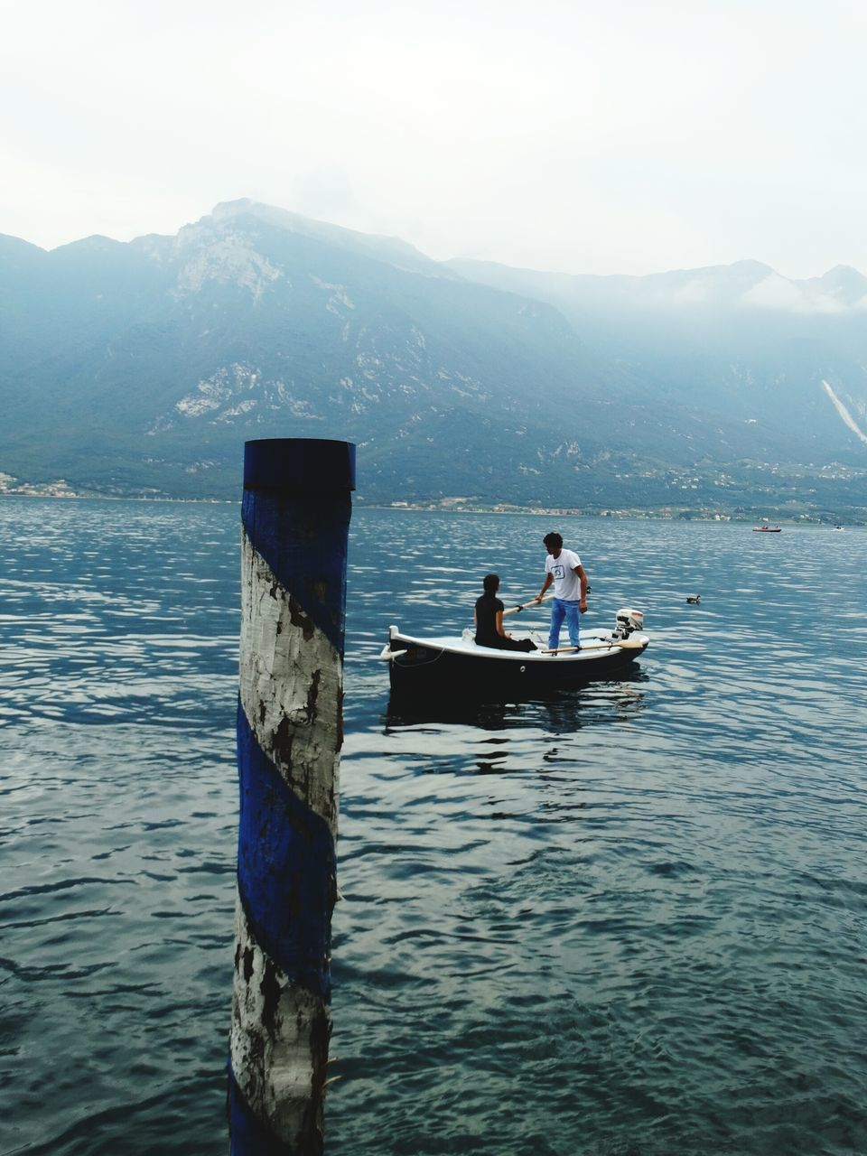 mountain, two people, nature, water, day, men, scenics, mountain range, real people, beauty in nature, outdoors, transportation, tranquility, leisure activity, sitting, togetherness, sea, nautical vessel, sky, full length, young women, young adult, adult, people