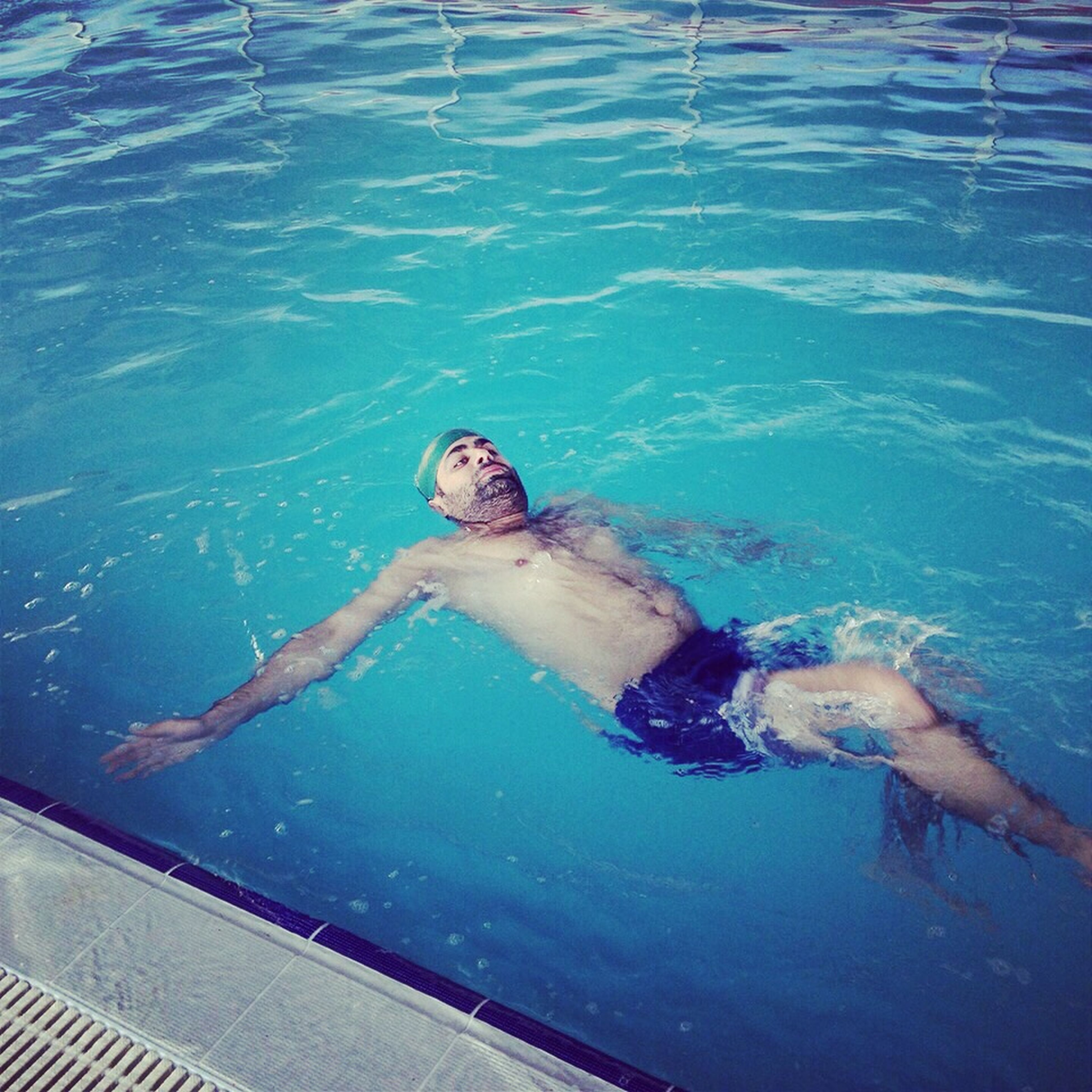 water, swimming pool, high angle view, blue, lifestyles, swimming, leisure activity, sea, full length, low section, relaxation, sitting, turquoise colored, day, men, sunlight, person, one animal