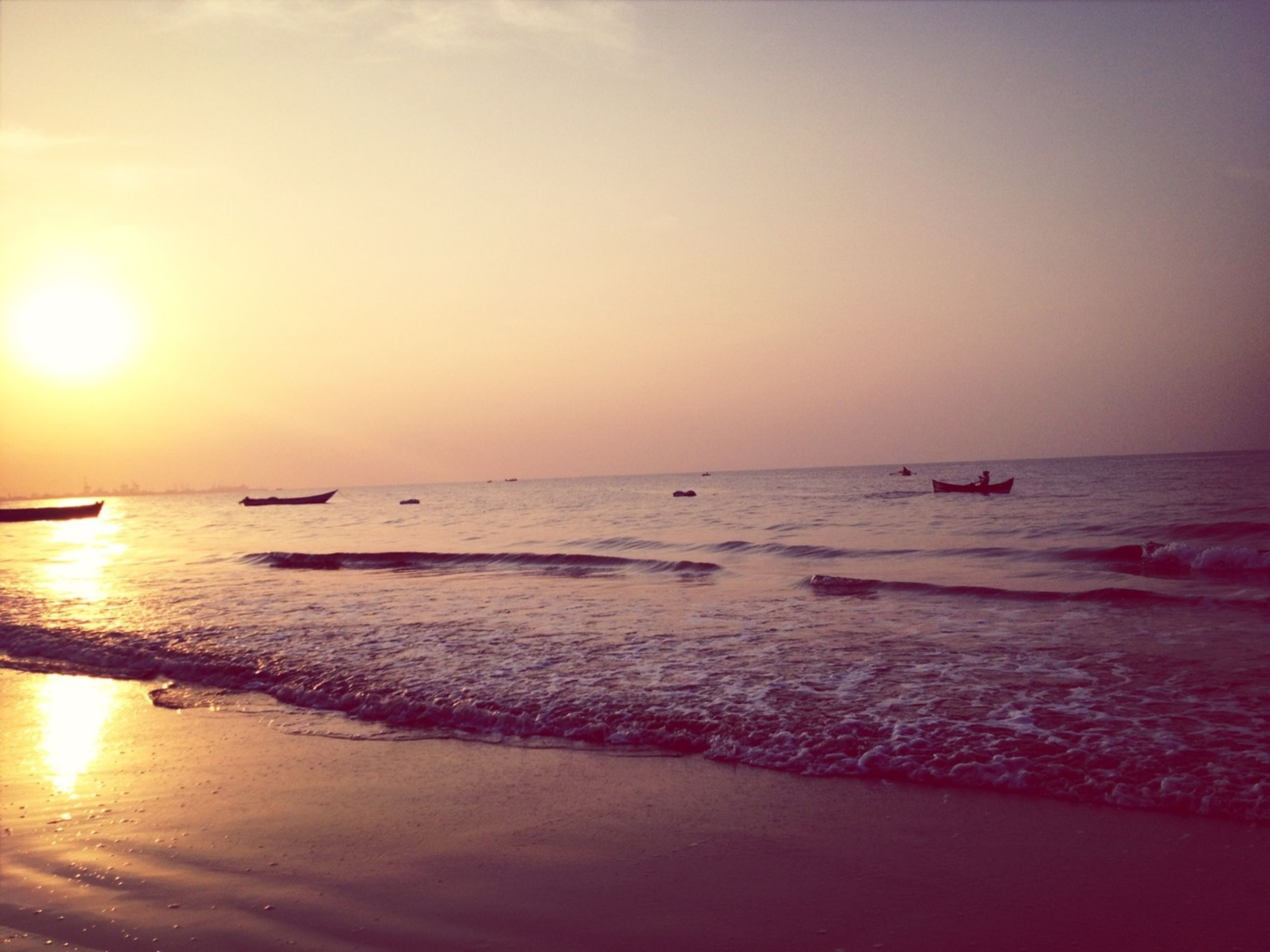 sea, horizon over water, water, sunset, beach, scenics, tranquil scene, beauty in nature, tranquility, sun, nautical vessel, shore, idyllic, nature, orange color, boat, transportation, sky, clear sky, reflection