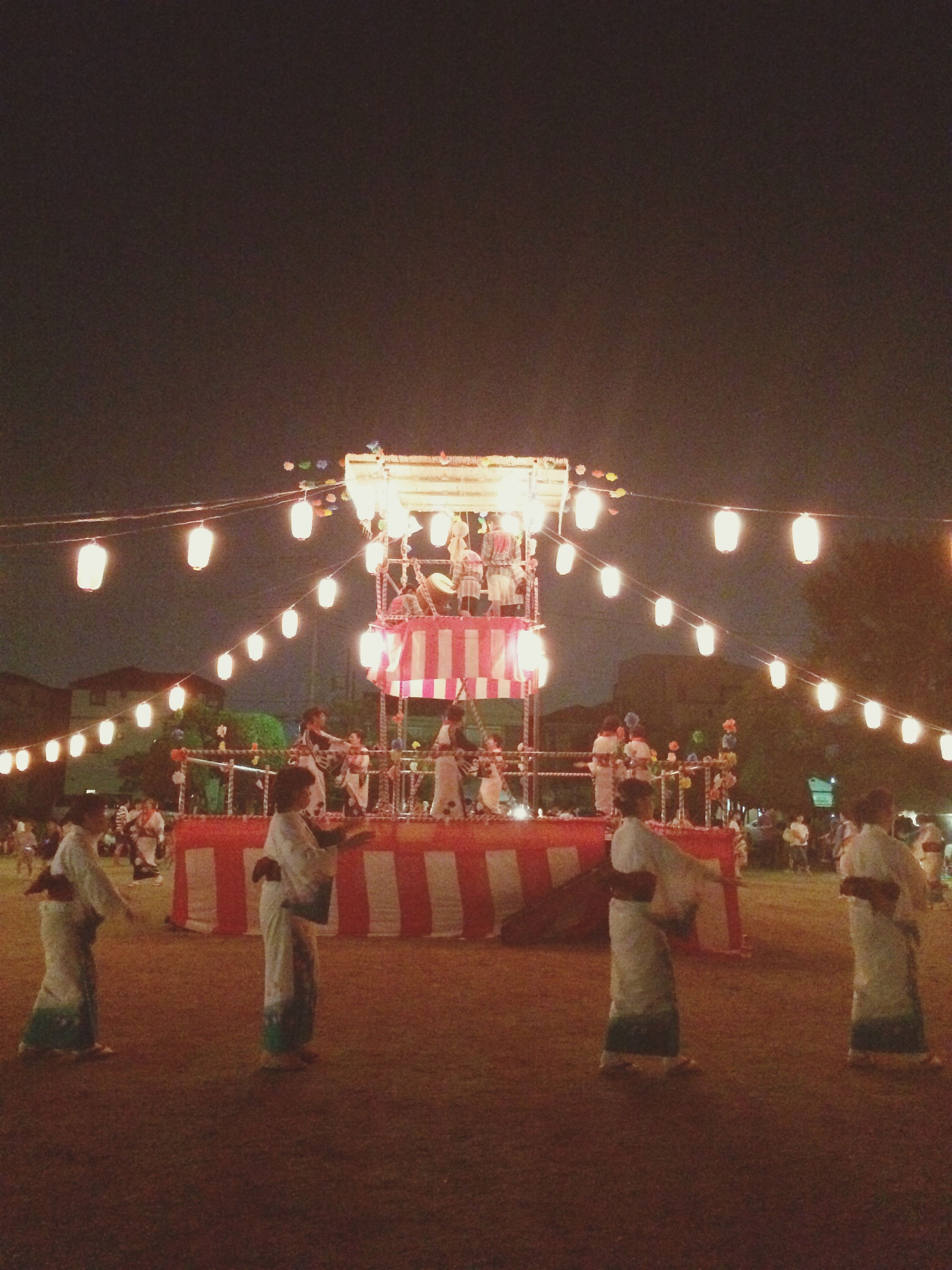 illuminated, lifestyles, night, leisure activity, large group of people, men, person, arts culture and entertainment, lighting equipment, celebration, enjoyment, fun, crowd, event, standing, mixed age range, rear view, performance, tradition