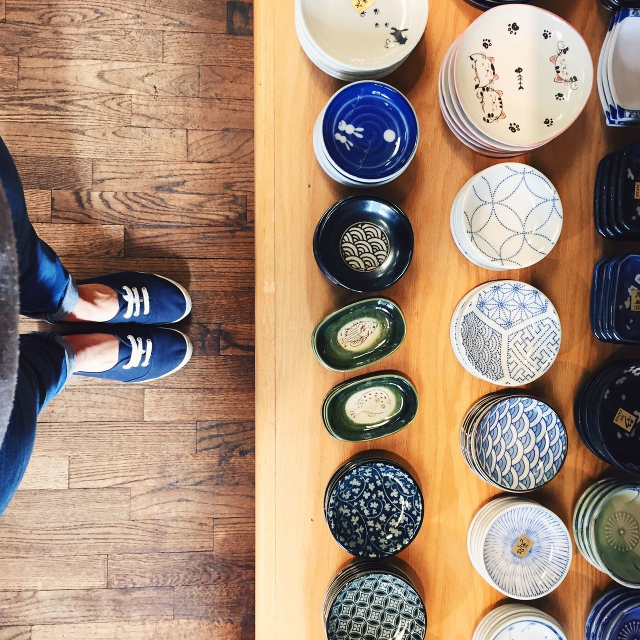 Woman standing in front of a shelf with Japanese pottery, San Francisco, USA. Adult Adults Only Blue California Close-up Day Human Body Part Human Leg Indoors  IPhone IPhoneography Japanese Culture Japanese Style Lifestyles Low Section One Person People Pottery Real People San Francisco Square USA View From Above Women