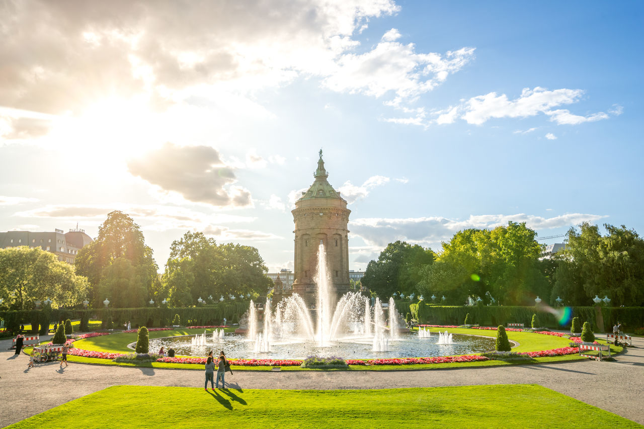 fountain, architecture, tree, sky, built structure, water, cloud - sky, motion, real people, outdoors, travel, building exterior, leisure activity, travel destinations, spraying, men, grass, large group of people, day, city, nature, people