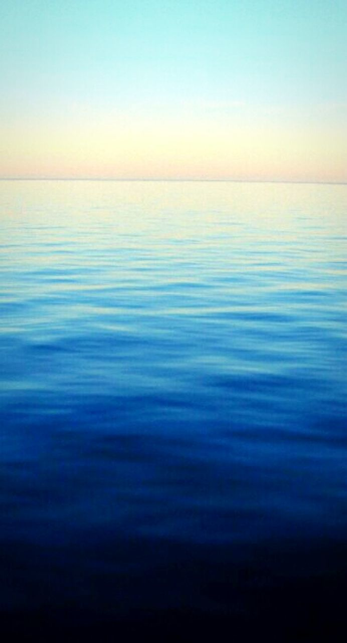 sea, water, blue, tranquil scene, scenics, reflection, nature, horizon over water, beauty in nature, tranquility, backgrounds, idyllic, sky, sunset, vibrant color, rippled, clear sky, no people, perfection, beach, abstract, outdoors, vacations, awe, horizon, sunlight, relaxation, beauty, multi colored, wave, above, day
