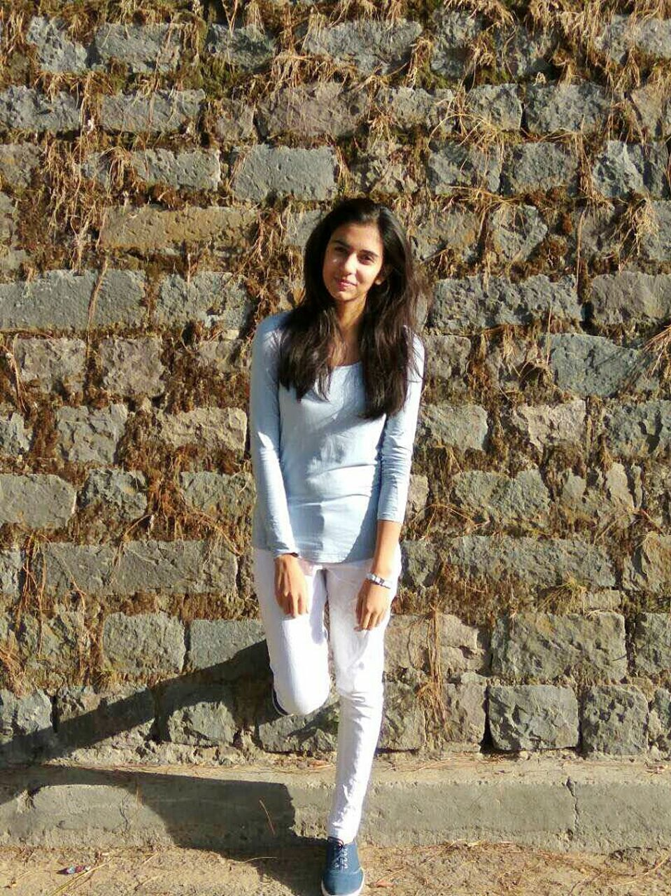 looking at camera, one person, portrait, standing, full length, young adult, front view, casual clothing, real people, long hair, day, young women, outdoors, leisure activity, smiling, beautiful woman, lifestyles, medium-length hair, one young woman only, one woman only, adult, people, adults only