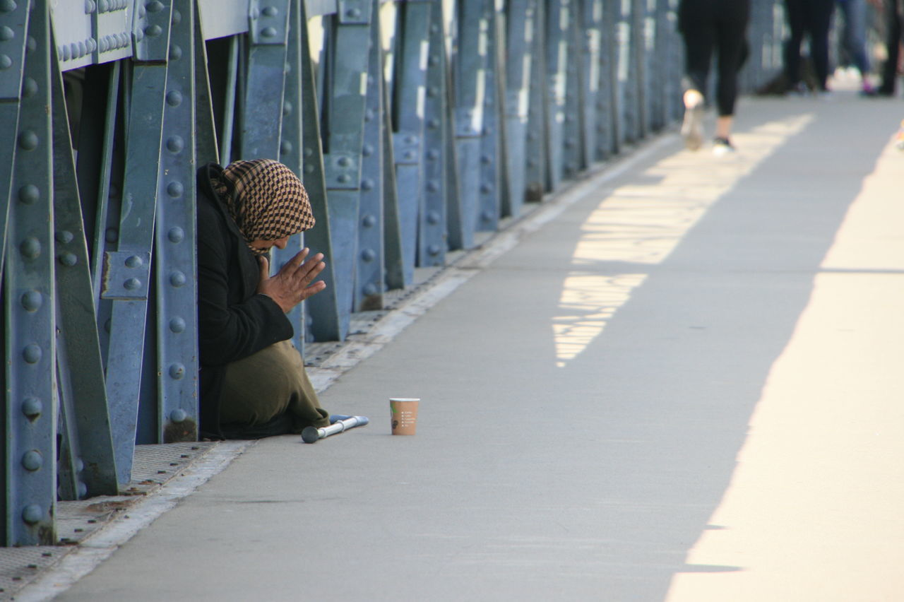 Side View Of Woman Begging On Bridge