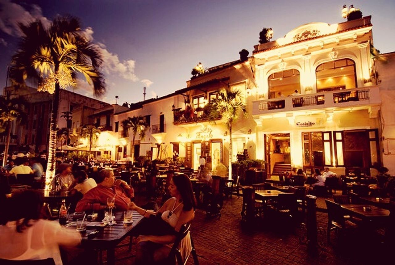 cafe, restaurant, bar - drink establishment, sidewalk cafe, dusk, people, city, food and drink, architecture, food and drink industry, nightlife, men, large group of people, adult, building exterior, night, outdoors, adults only, happy hour, sky