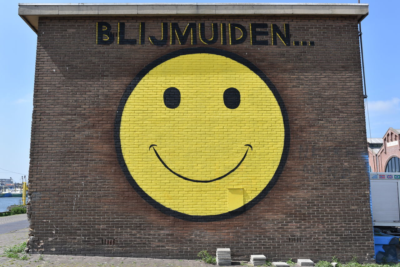 Antropomorphic Architecture Building Exterior Built Structure Close-up Communication Day Guidance Happy Happy :) Human Representation Neighborhood Neighborhood Map No People Outdoors Road Sign Sky Smiley Smiley Face Yellow