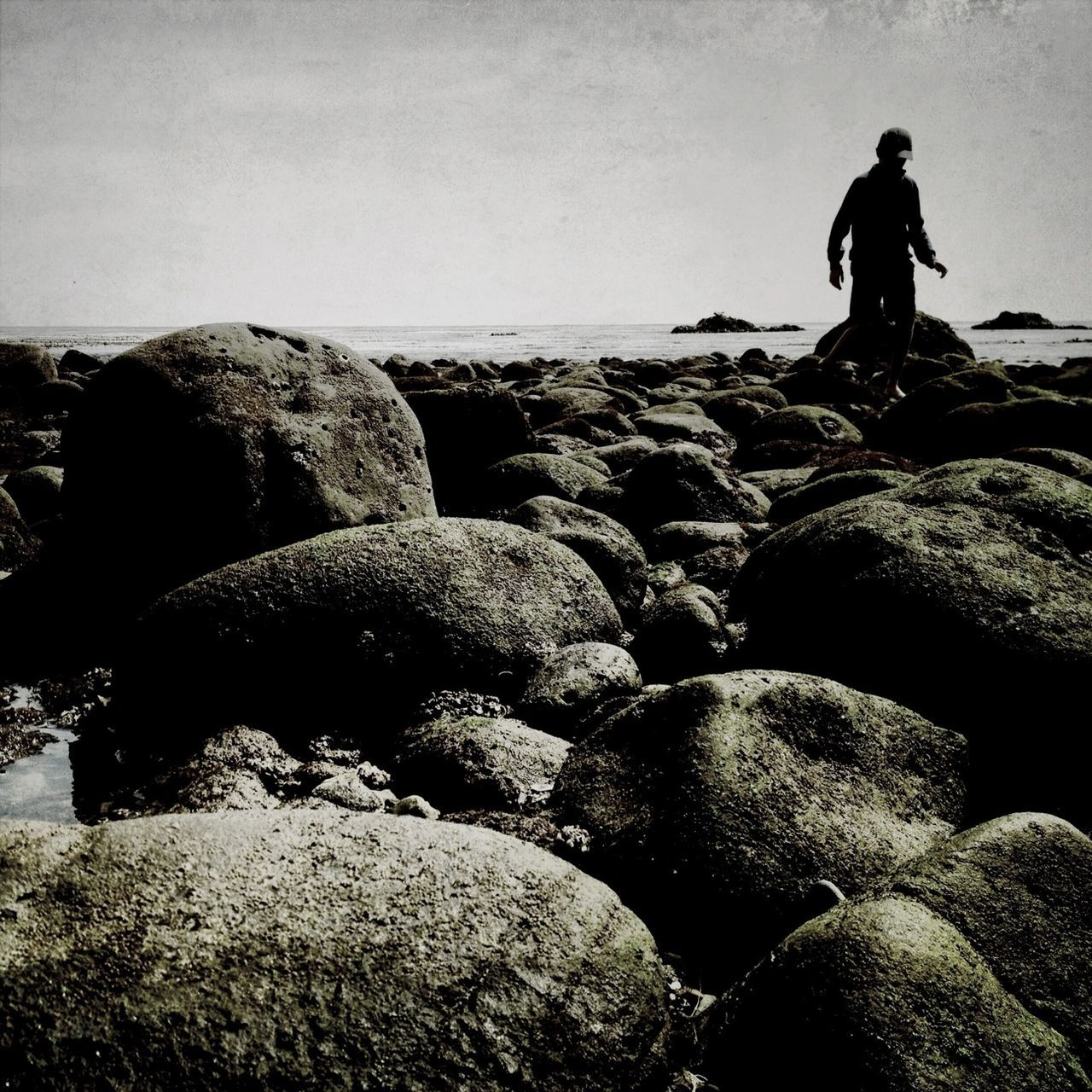 Man Standing On Rocks Against Sky At Dusk