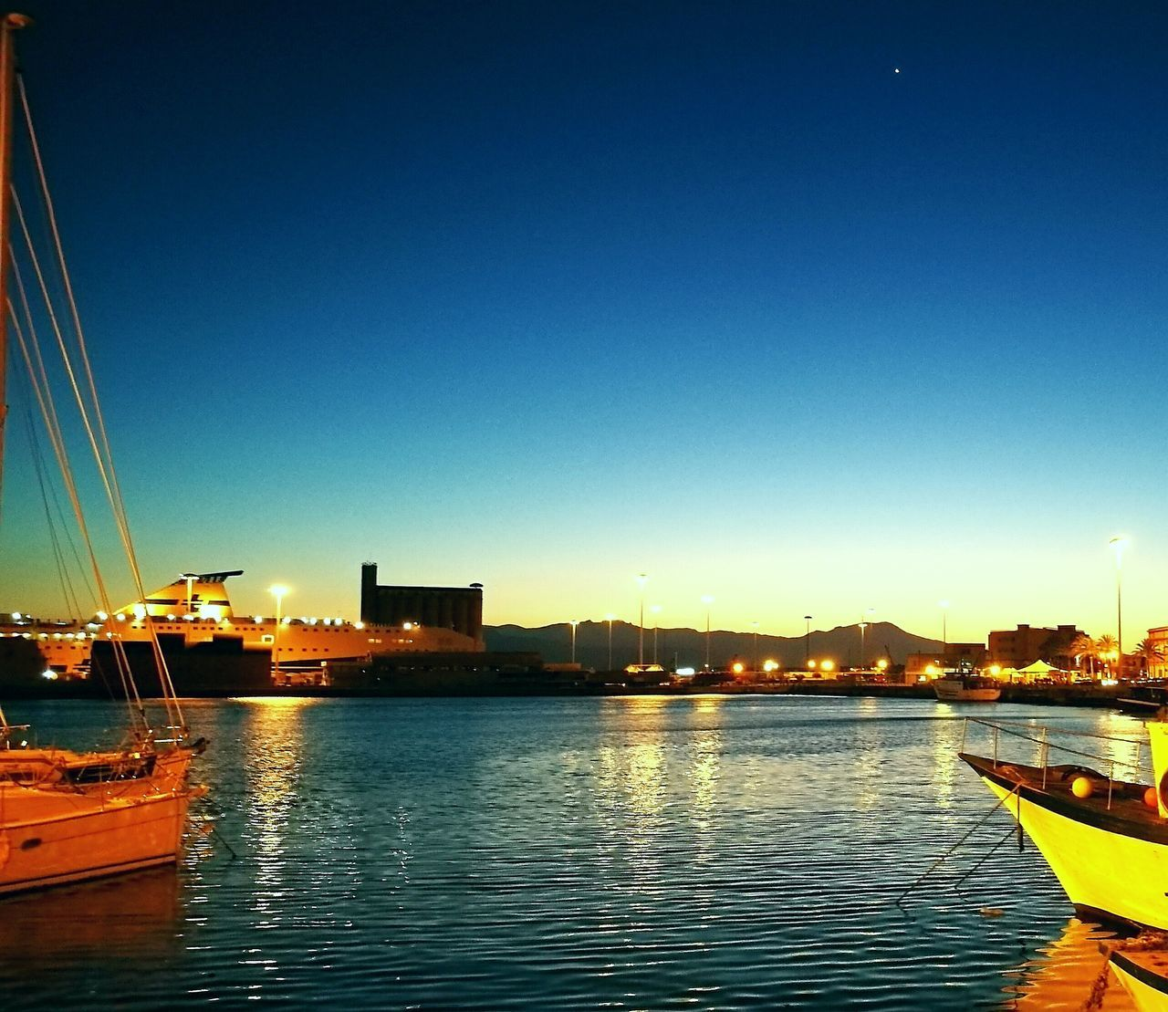 nautical vessel, transportation, water, mode of transport, moored, river, boat, no people, harbor, illuminated, blue, reflection, outdoors, building exterior, marina, waterfront, built structure, architecture, sunset, city, yacht, travel destinations, sky, clear sky, night, sailboat, nature, mast, commercial dock, beauty in nature