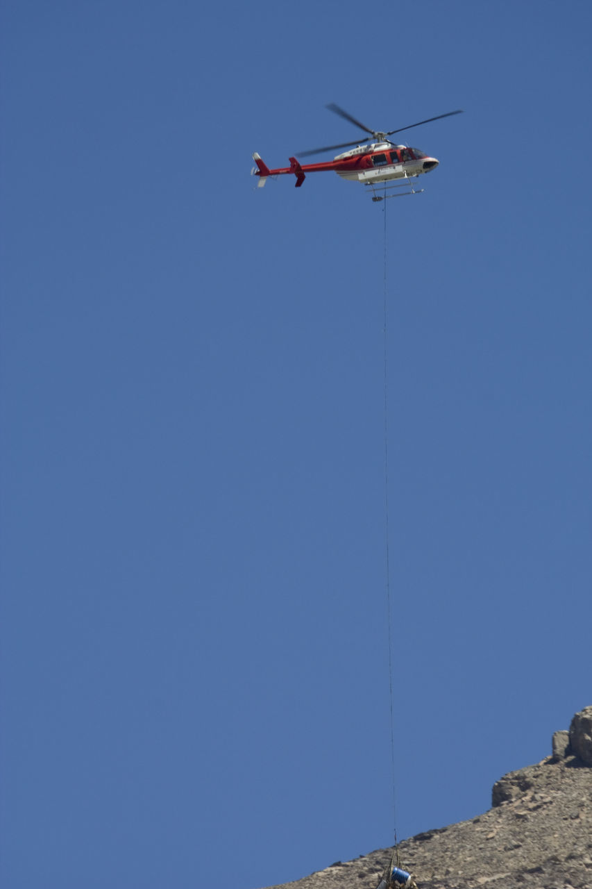 copy space, blue, low angle view, clear sky, mid-air, flying, mode of transport, transportation, helicopter, day, air vehicle, outdoors, airplane, men, real people, nature, one person, sky, people
