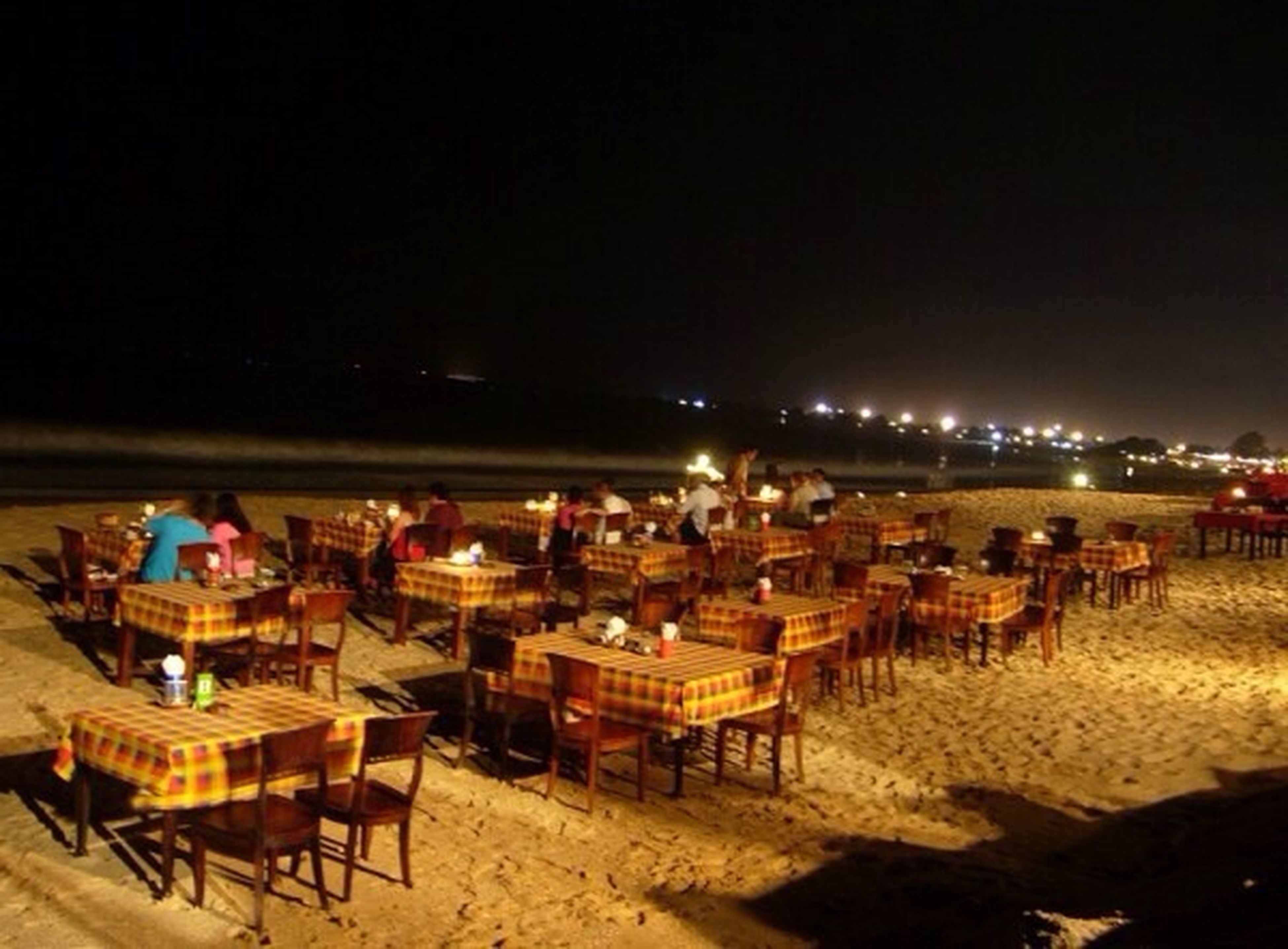 beach, sand, night, illuminated, chair, shore, copy space, clear sky, absence, sea, built structure, outdoors, relaxation, building exterior, empty, architecture, incidental people, tranquility, seat, nature