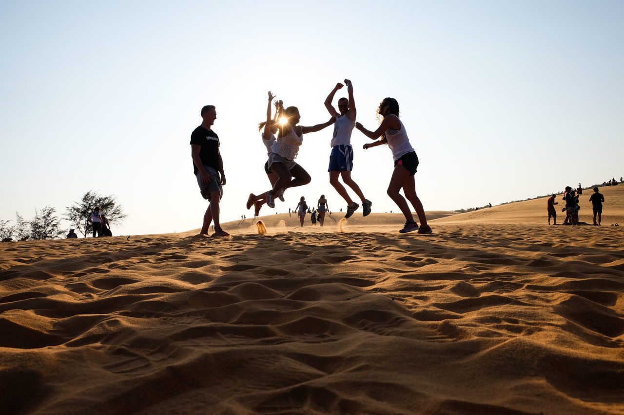 sand, beach, real people, leisure activity, fun, lifestyles, men, sand dune, enjoyment, sky, motion, activity, clear sky, outdoors, jumping, vacations, friendship, desert, full length, day, nature, competition, beach volleyball, energetic, people