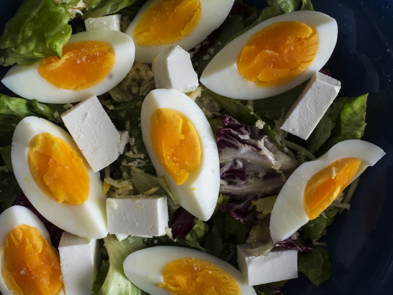 High angle view of green salad wth boiled eggs and feta cheese in blue bowl on a weathered old wooden table Asian Food Blue Boiled Bowl Cheese Close-up Day Egg Yolk Eggs Eggshell Feta Food Food And Drink Freshness Green Healthy Eating High Angle View Indoors  No People Plate Ready-to-eat Salad