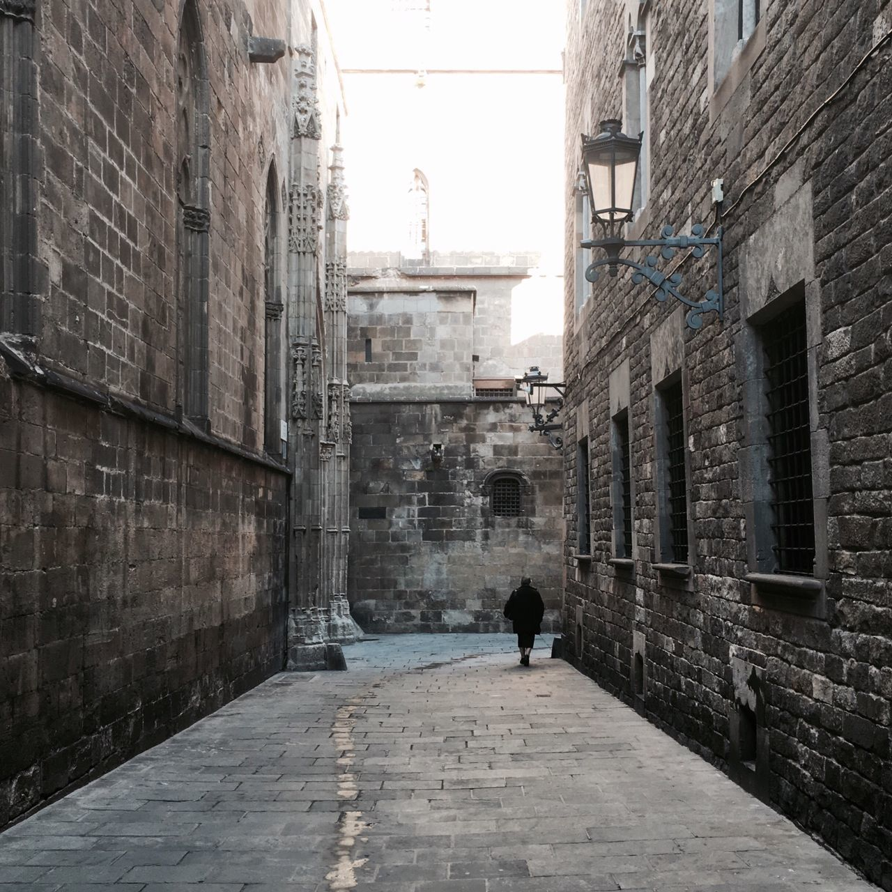 Rear View Of Woman Walking On Pathway Amidst Old Cathedral