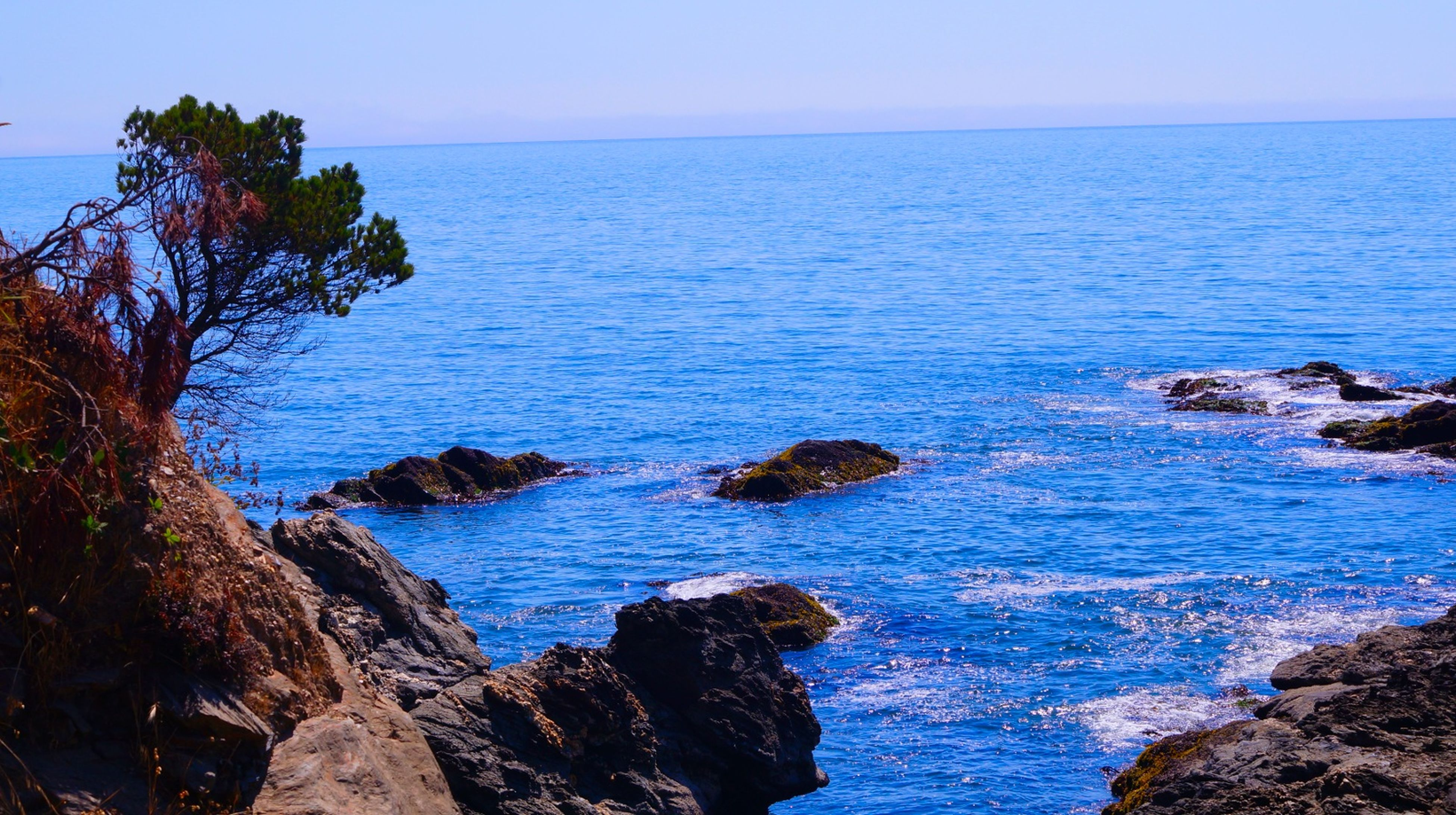 sea, horizon over water, water, tranquil scene, scenics, beauty in nature, tranquility, rock - object, blue, nature, beach, rock formation, sky, shore, clear sky, idyllic, coastline, rock, cliff, seascape