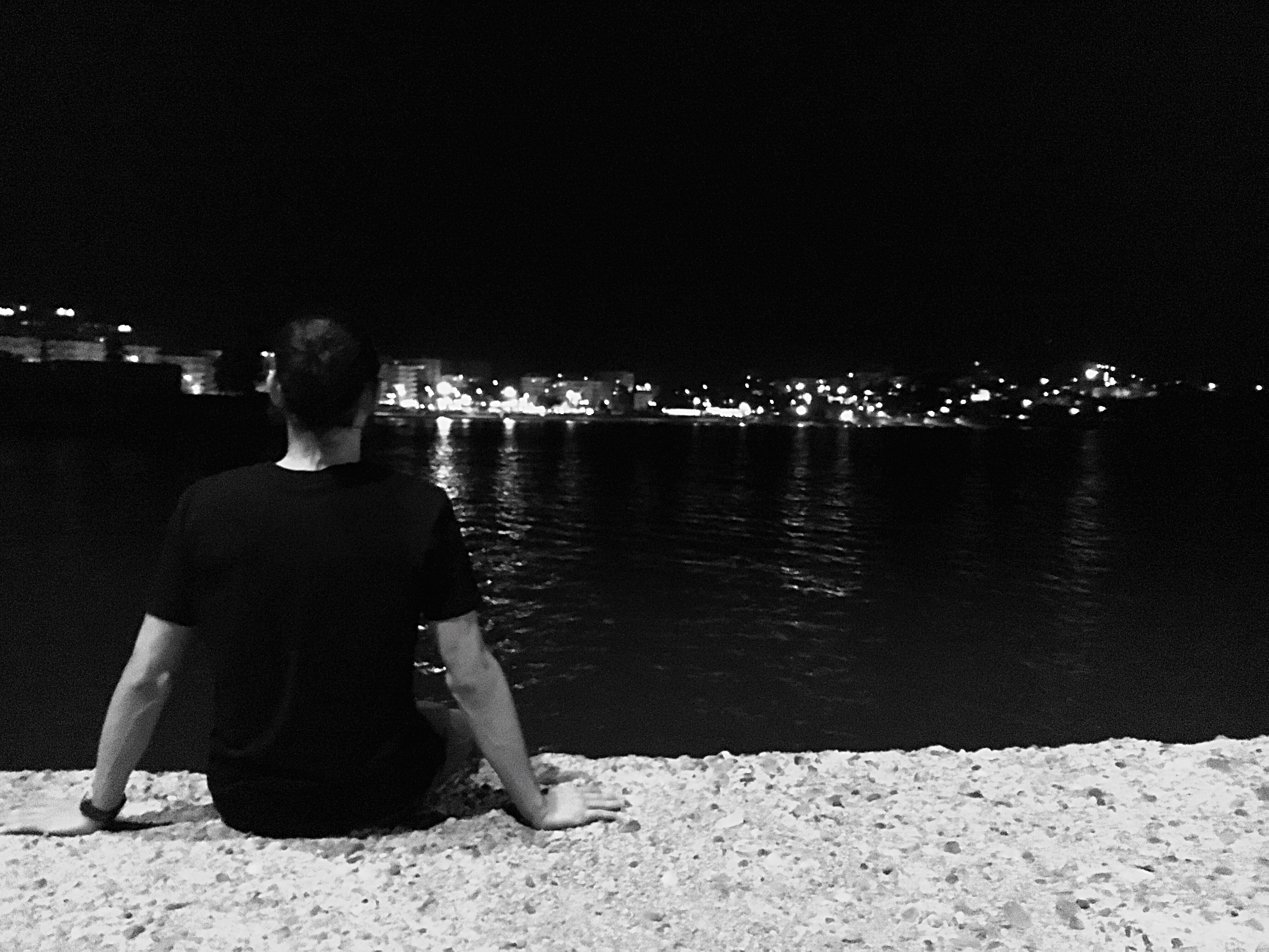 rear view, water, illuminated, sitting, night, men, relaxation, waist up, solitude, clear sky, tranquility, tranquil scene, calm, sea, vacations, getting away from it all, in front of, dark, scenics, remote