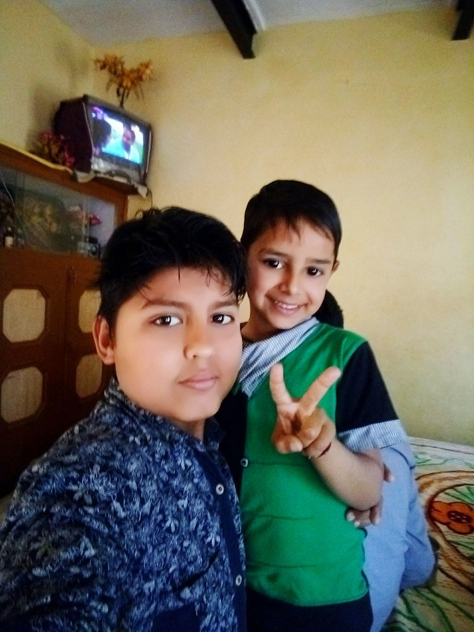 looking at camera, childhood, real people, togetherness, boys, elementary age, family with one child, indoors, family, mother, portrait, love, bonding, smiling, home interior, girls, leisure activity, daughter, happiness, lifestyles, son, casual clothing, front view, cute, bed, young adult, day