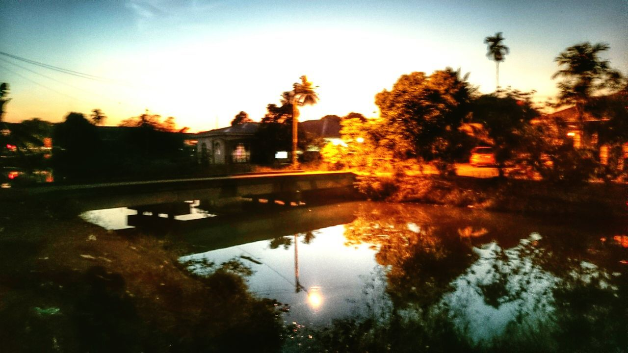 reflection, water, tree, sunset, no people, outdoors, sky, nature, architecture, built structure, puddle, building exterior, beauty in nature, day