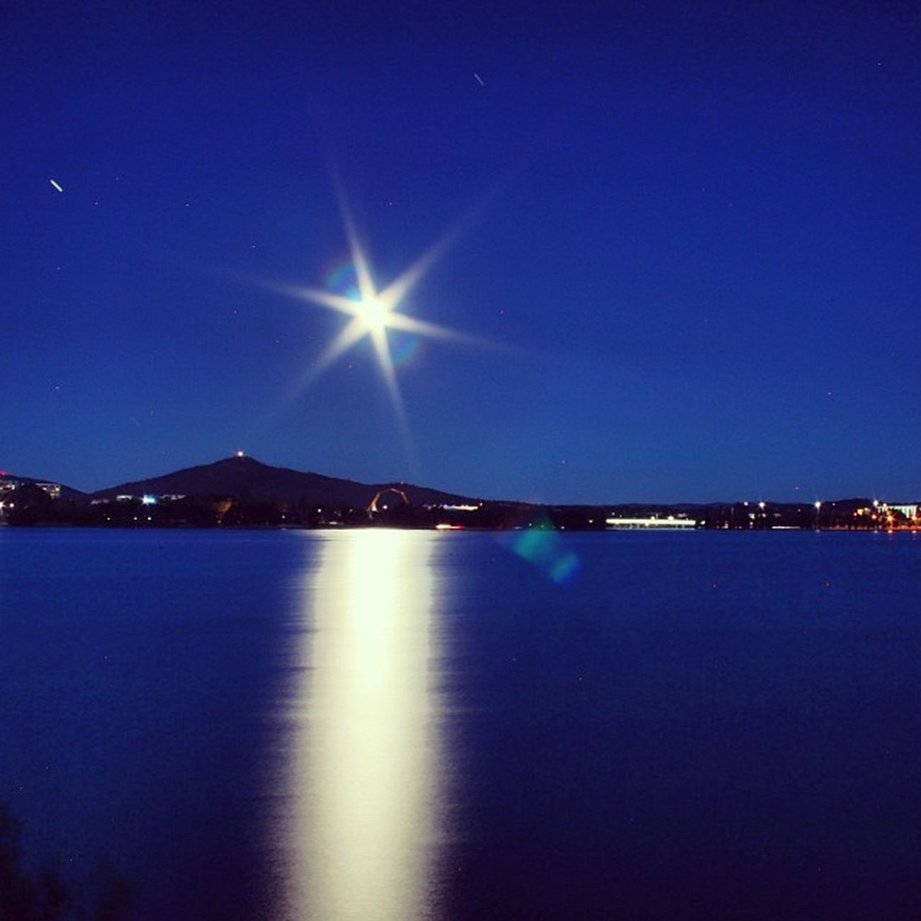 Full moon over Mount Ainslie and over the lake