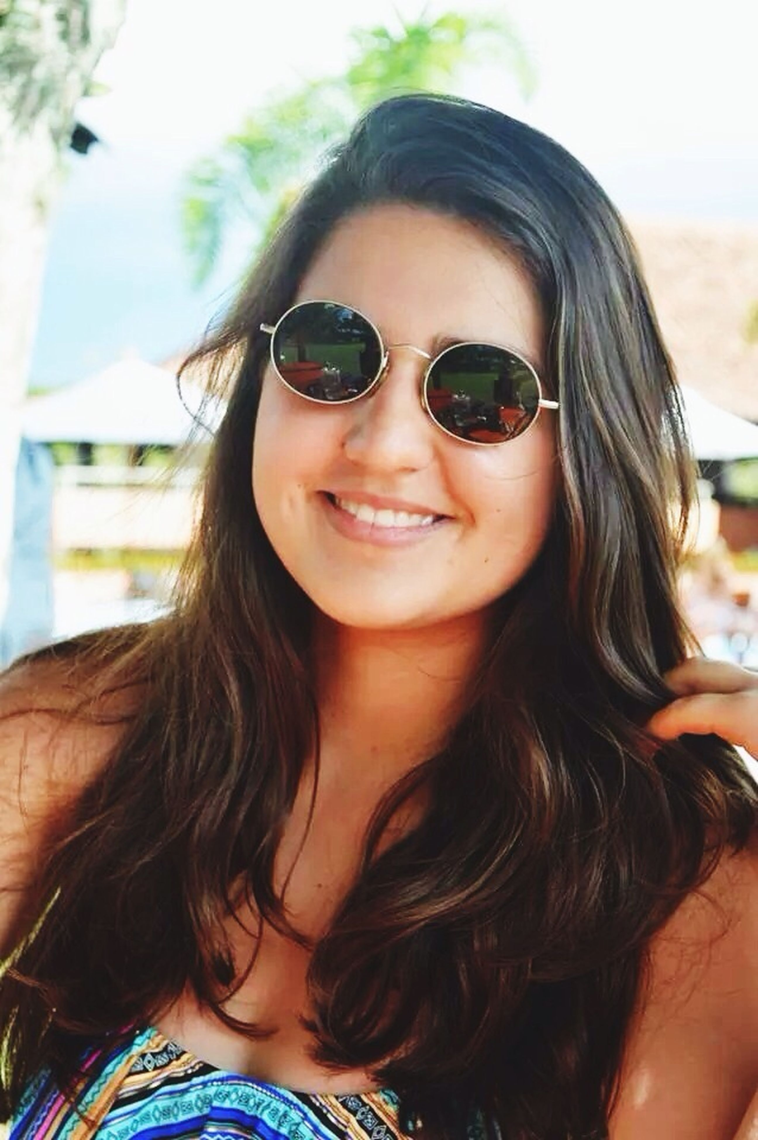young women, young adult, long hair, portrait, person, looking at camera, headshot, lifestyles, leisure activity, smiling, sunglasses, focus on foreground, front view, head and shoulders, brown hair, close-up, happiness