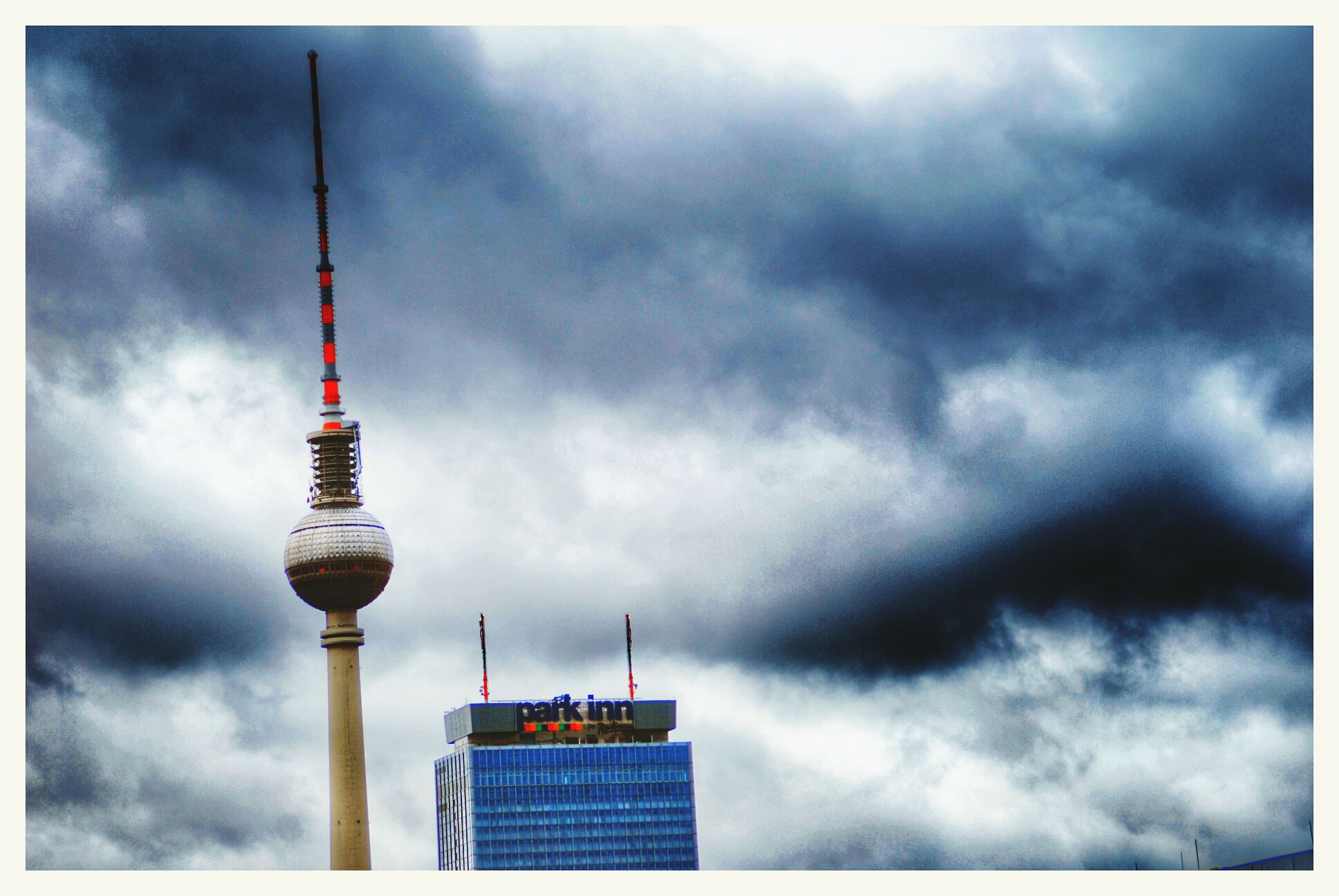 sky, architecture, built structure, tower, cloud - sky, building exterior, low angle view, cloudy, tall - high, communications tower, communication, transfer print, auto post production filter, weather, cloud, city, travel destinations, capital cities, overcast, tall
