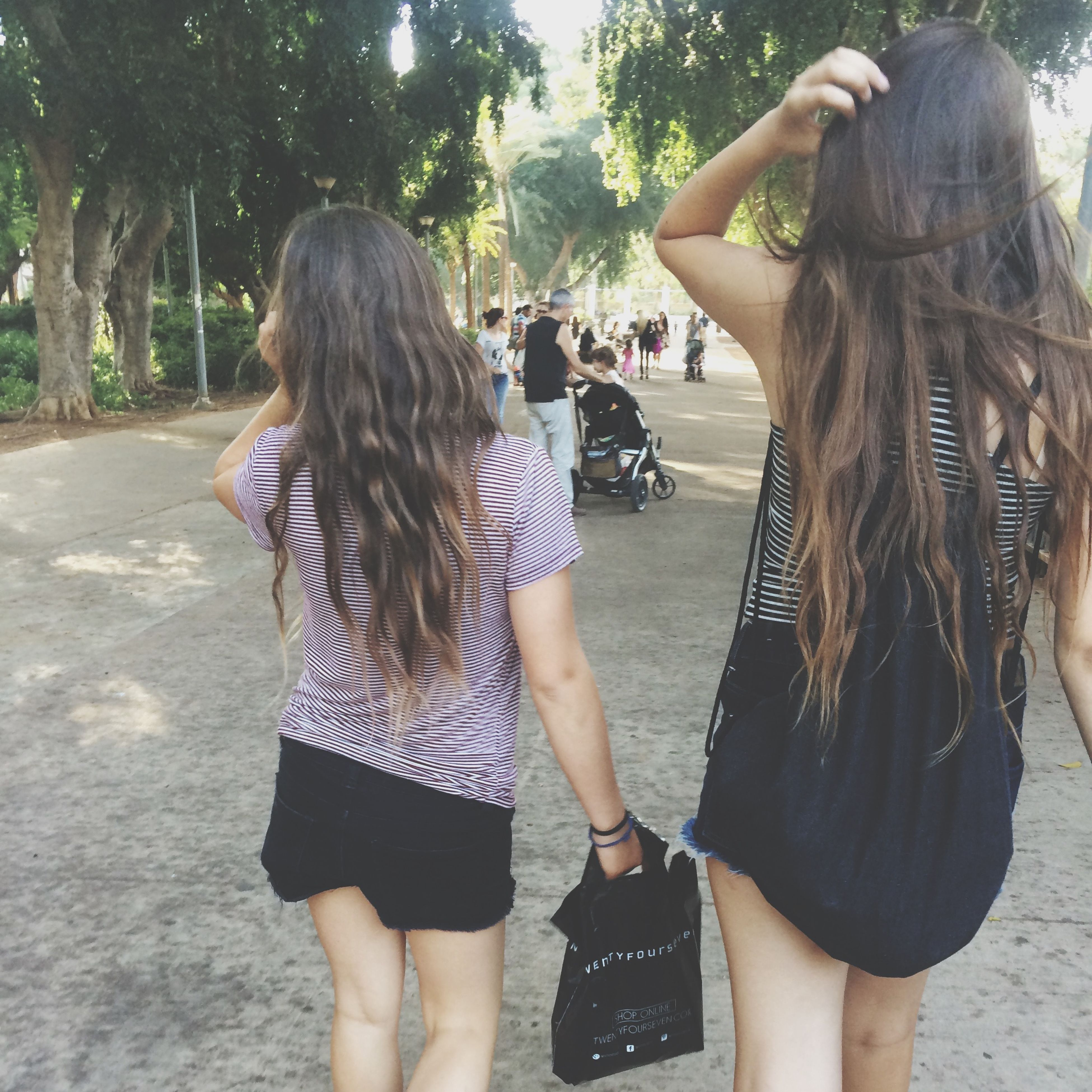 lifestyles, leisure activity, person, togetherness, casual clothing, rear view, standing, bonding, friendship, young women, tree, three quarter length, sunlight, young adult, day, long hair, full length