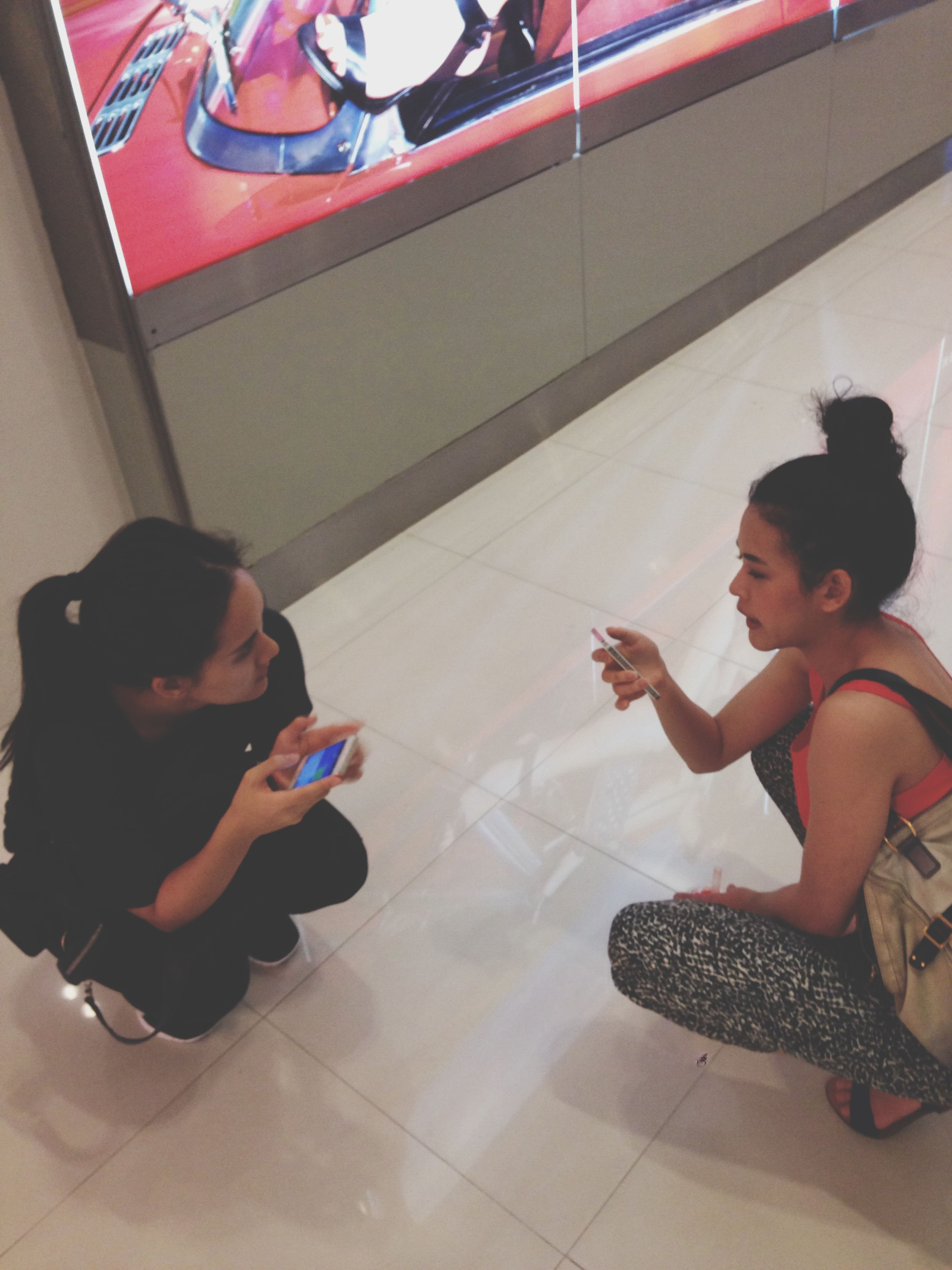 indoors, lifestyles, leisure activity, person, casual clothing, young adult, full length, childhood, sitting, young women, home interior, happiness, togetherness, fun, holding, high angle view, smiling