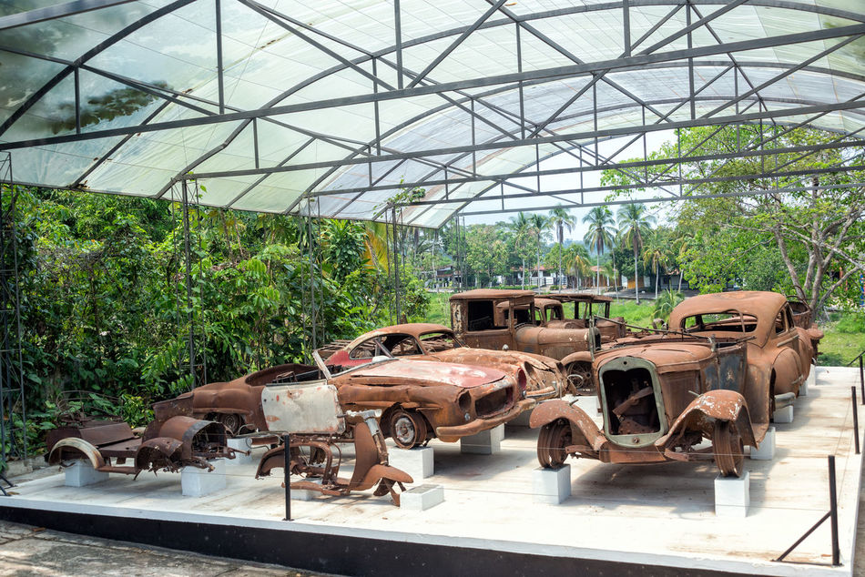 PUERTO TRIUNFO, COLOMBIA - FEBRUARY 26: A destroyed collection of cars that once belonged to Pablo Escobar on display in Puerto Triunfo, Colombia on February 26, 2014. Pablo Escobar was a cocaine trafficker who became one of the richest men in the world Abandoned Antique Auto Automobile Burned Burnt Car Cars Classic Collection Damaged Day Display Escobar Front Hacienda Indoors  Napoles Old Pablo Retro Transport Transportation Vehicle Vintage