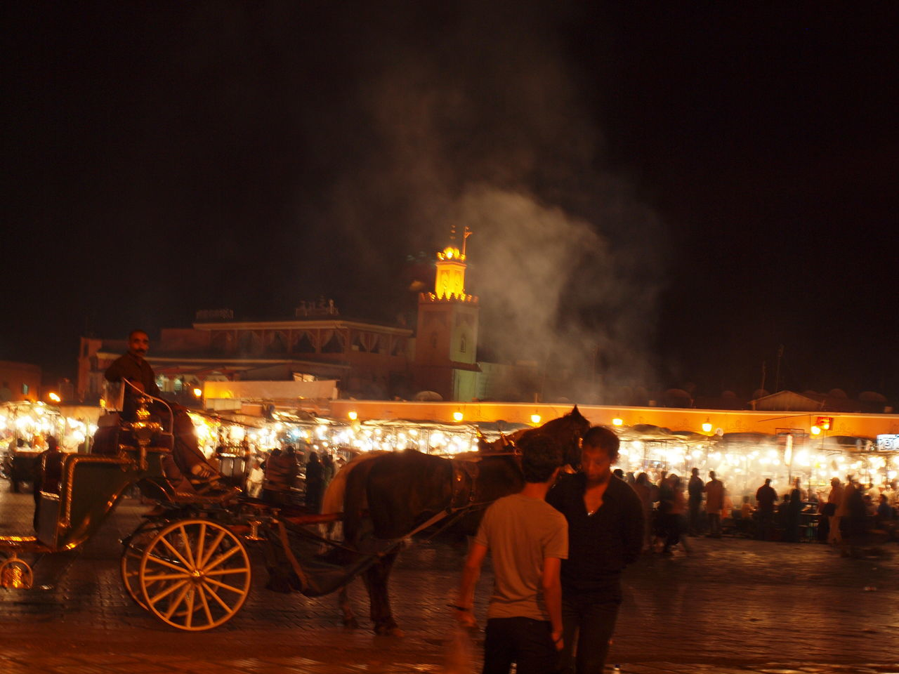 night, illuminated, real people, built structure, transportation, horse cart, mode of transport, sky, men, architecture, large group of people, outdoors, women, building exterior, domestic animals, mammal, people
